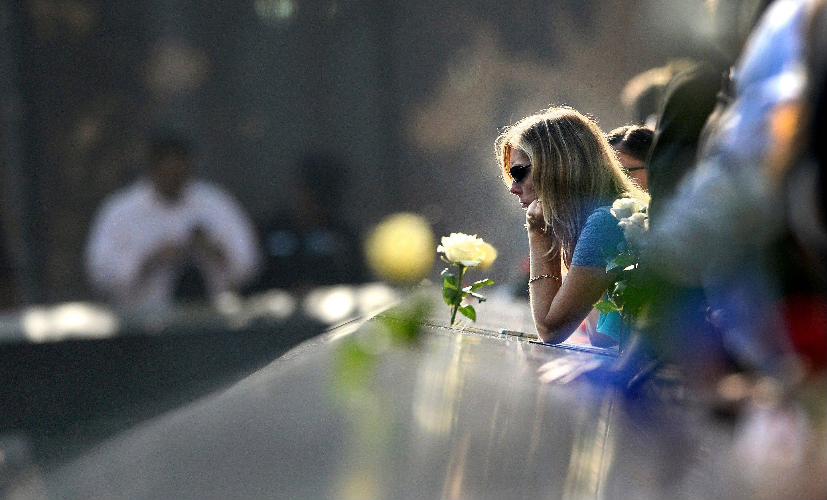 A woman pauses along the edge of the north reflecting pool at the Sept. 11 memorial during a ceremony marking the 12th anniversary of the 9/11 attacks on the World Trade Center in New York, September 11, 2013.