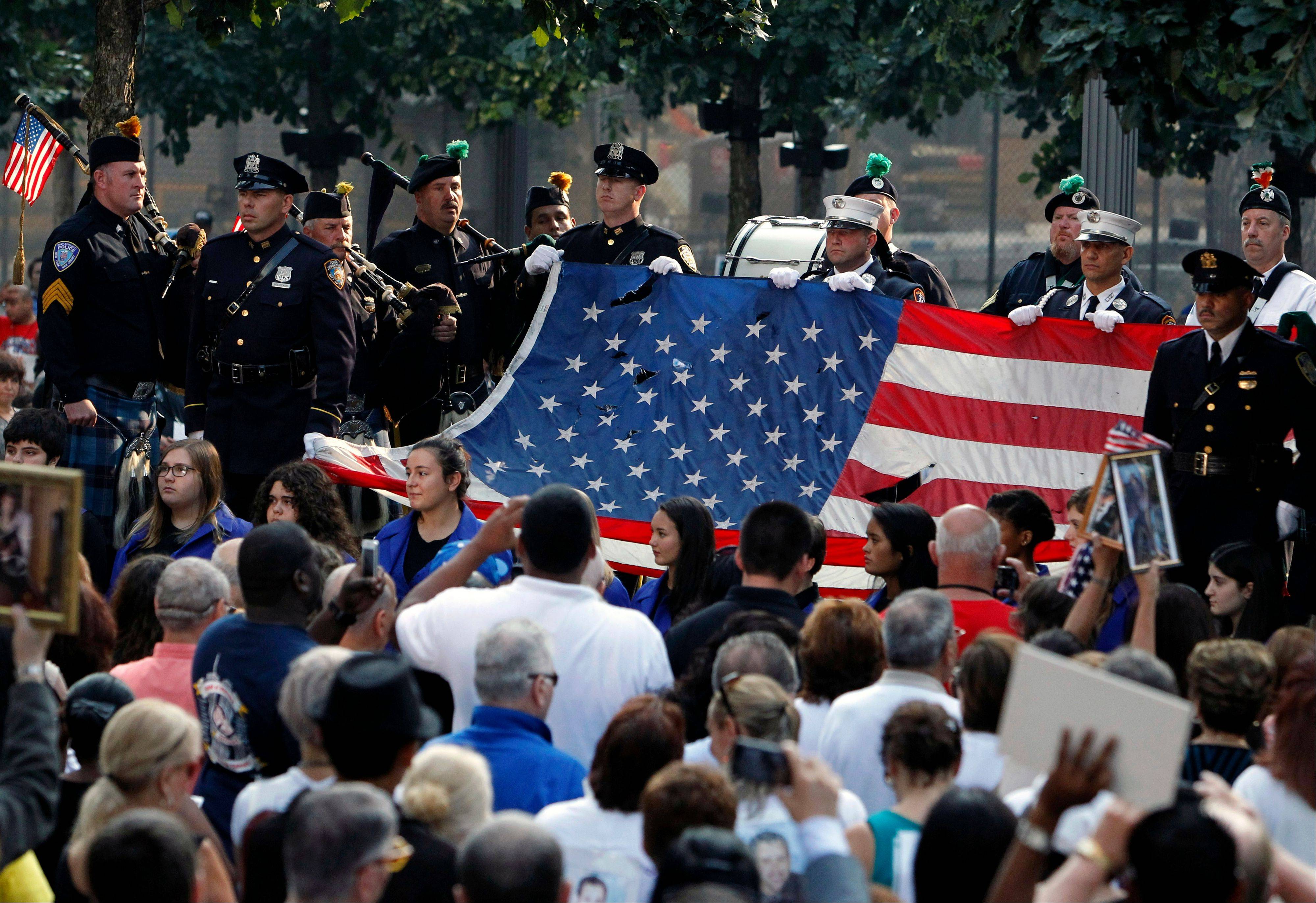 The World Trade Center Flag is presented as friends and relatives of the victims of the 9/11 terrorist attacks gather at the National September 11 Memorial at the World Trade Center site, Wednesday, Sept. 11, 2013, for a ceremony marking the 12th anniversary of the attacks in New York.