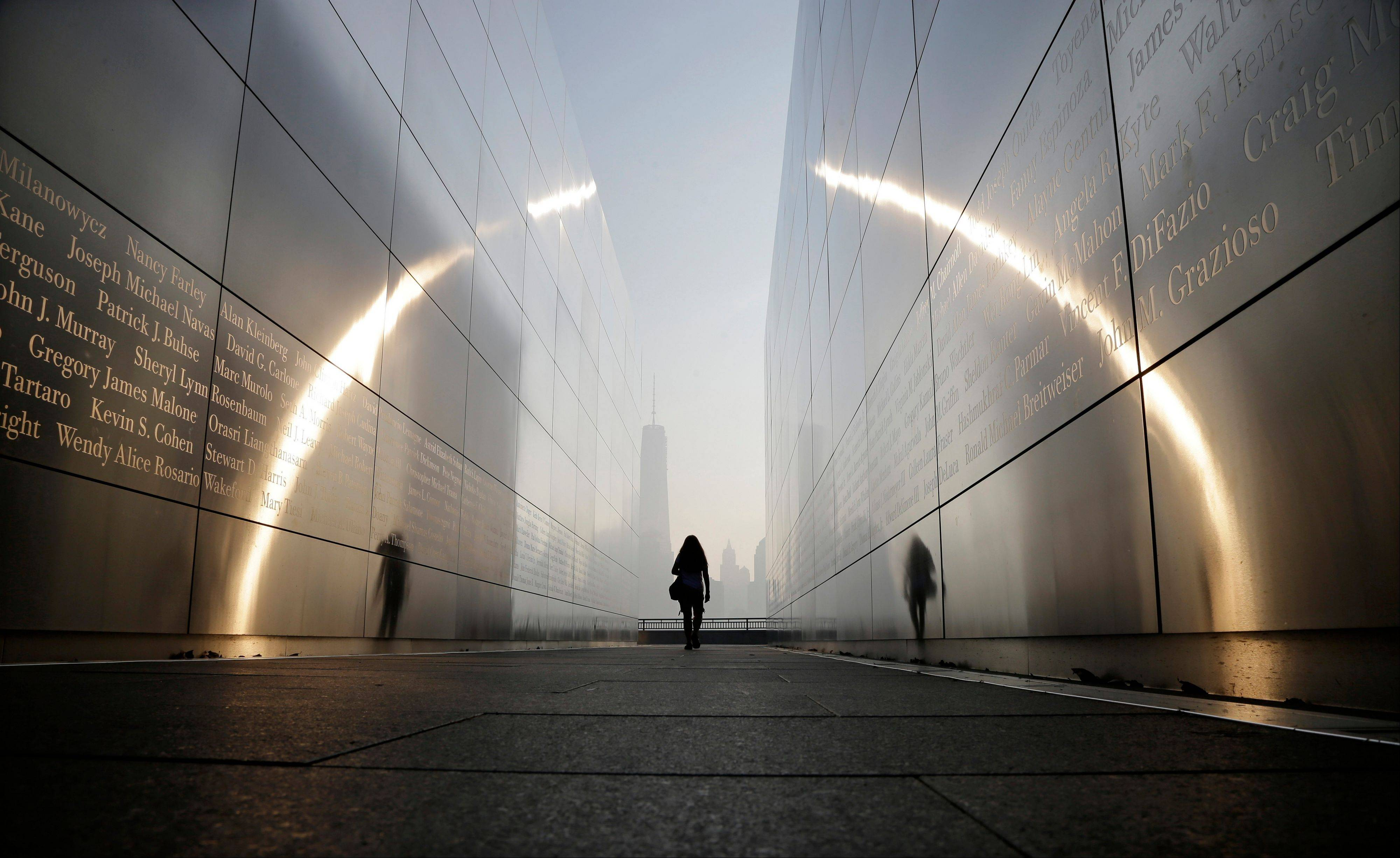 "A visitor walks through the ""Empty Sky"" memorial to New Jersey's victims of the Sept. 11, 2001 terrorist attacks on Wednesday, Sept. 11, 2013, in Jersey City, N.J. One World Trade Center is visible across the Hudson River. Ceremonies will be held Wednesday to mark the 12th anniversary of the attacks."