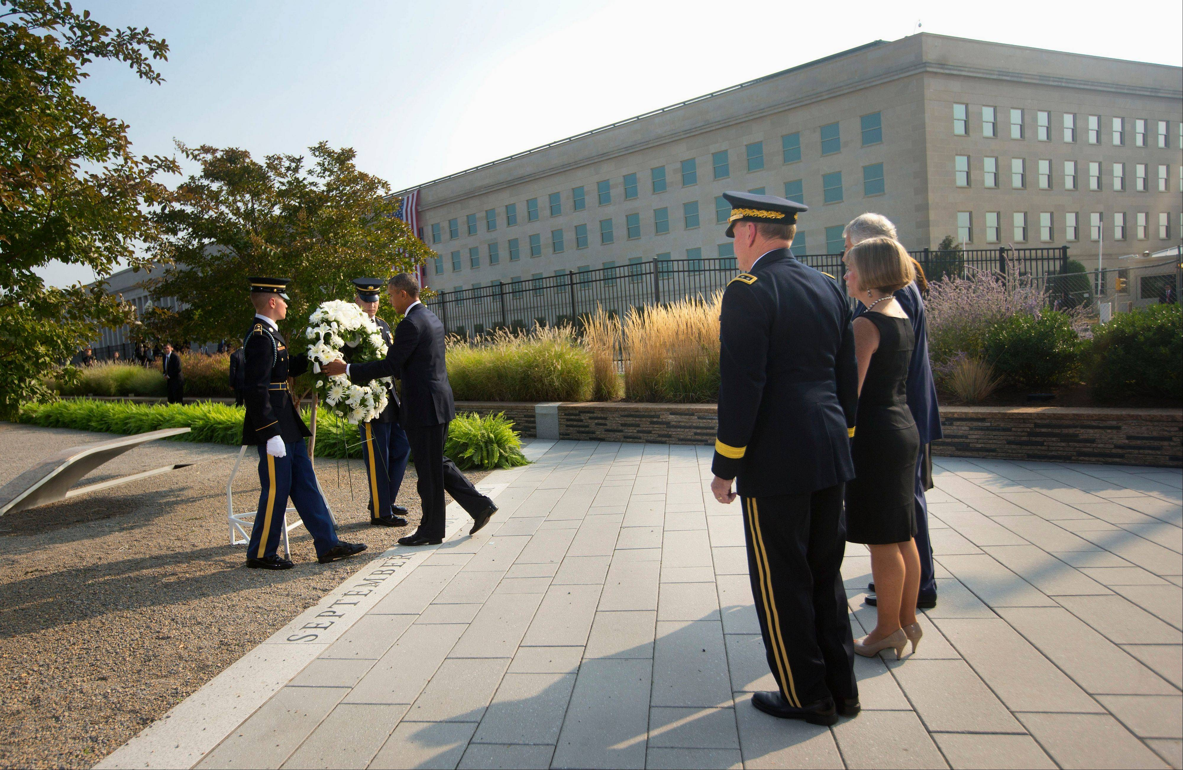 President Barack Obama places a wreath at the Pentagon Sept. 11 memorial, as Joint Chiefs Chairman Gen. Martin Dempsey, his wife Deanie Dempsey and Defense Secretary Chuck Hagel, watch Wednesday, Sept. 11, 2013, at the Pentagon during a ceremony to mark the 12th anniversary of the 9/11 attacks.