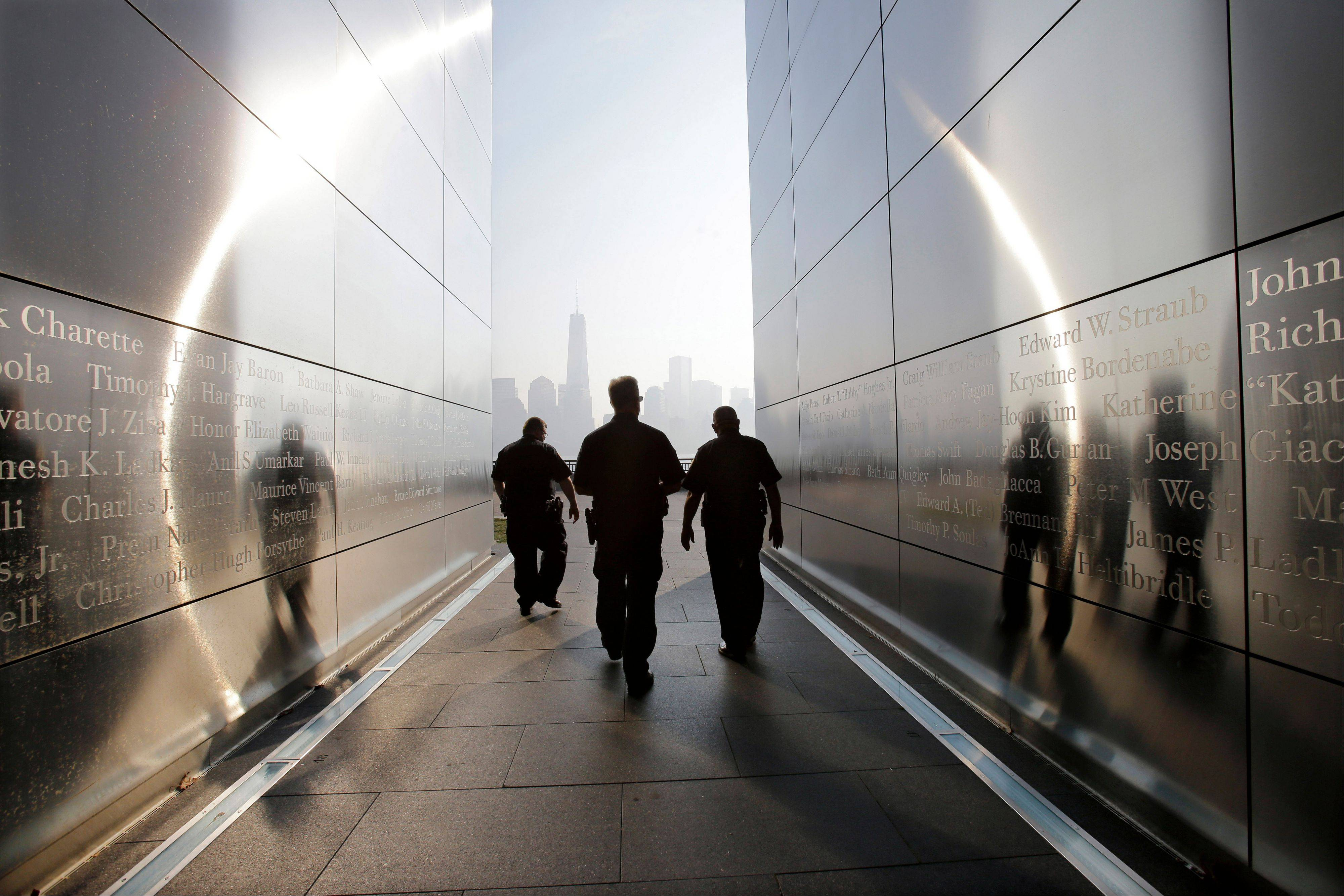 "Three police officers walk through the ""Empty Sky"" memorial to New Jersey's victims of the Sept. 11, 2001 terrorist attacks on Wednesday, Sept. 11, 2013, in Jersey City, N.J. Ceremonies will be held Wednesday to mark the 12th anniversary of the attacks."