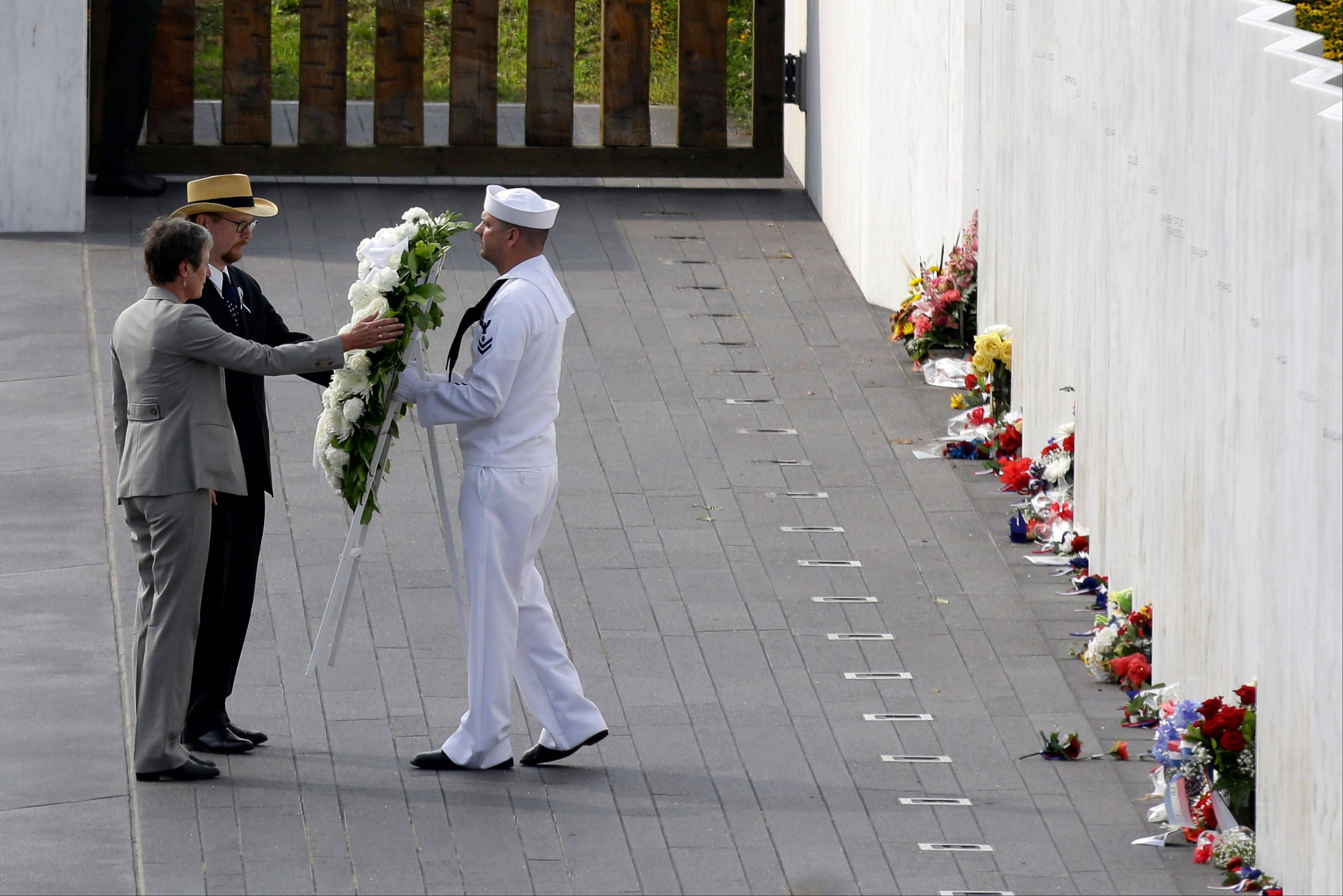 Secretary of the Interior Sally Jewell, left, and Gordon Felt, center, whose brother Edward P. Felt was a passenger on Flight 93, place a wreath with the help of Navy honor guard Matthew Konchan, of Johnstown, Pa., in front of the wall containing the names of the 40 crew and passengers on Flight 93 at the Flight 93 National Memorial on Wednesday, Sept. 11, 2013 in Shanksville.