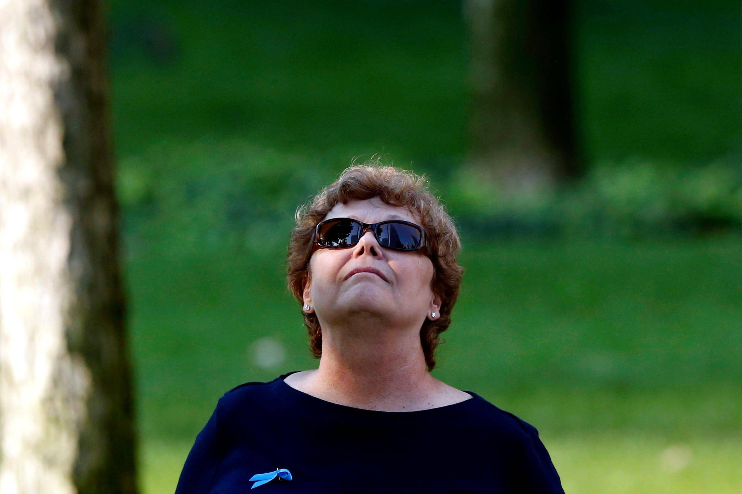 A woman looks to the sky during a moment of silence as friends and relatives of the victims of the 9/11 terrorist attacks gather at the National September 11 Memorial at the World Trade Center site, Wednesday, Sept. 11, 2013, for a ceremony marking the 12th anniversary of the attacks in New York.