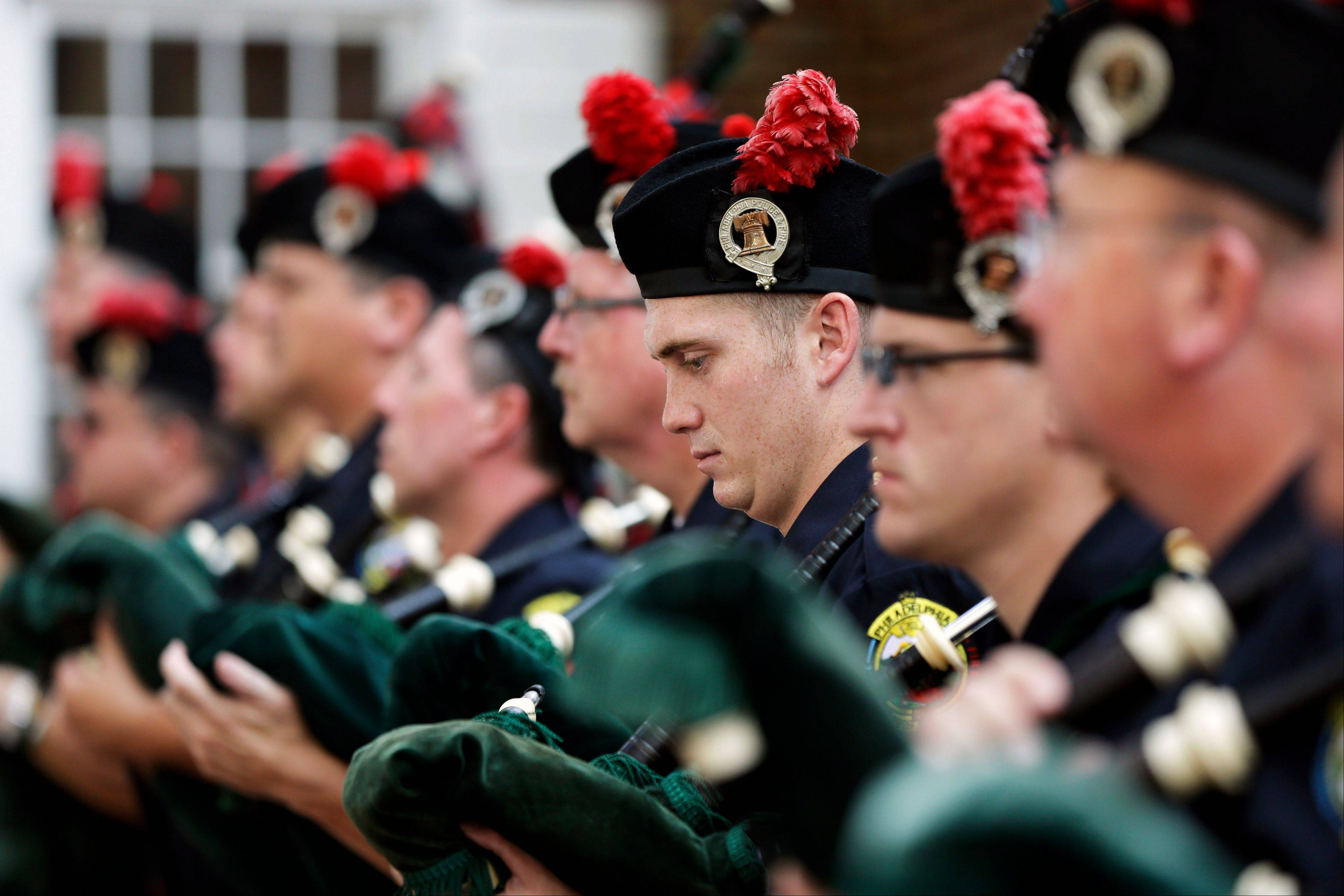Members of the Philadelphia Police & Fire Pipes & Drums listen to remarks during a ceremony Wednesday, Sept. 11, 2013, marking the 12th anniversary of the Sept. 11 terrorist attacks at the Betsy Ross House in Philadelphia.