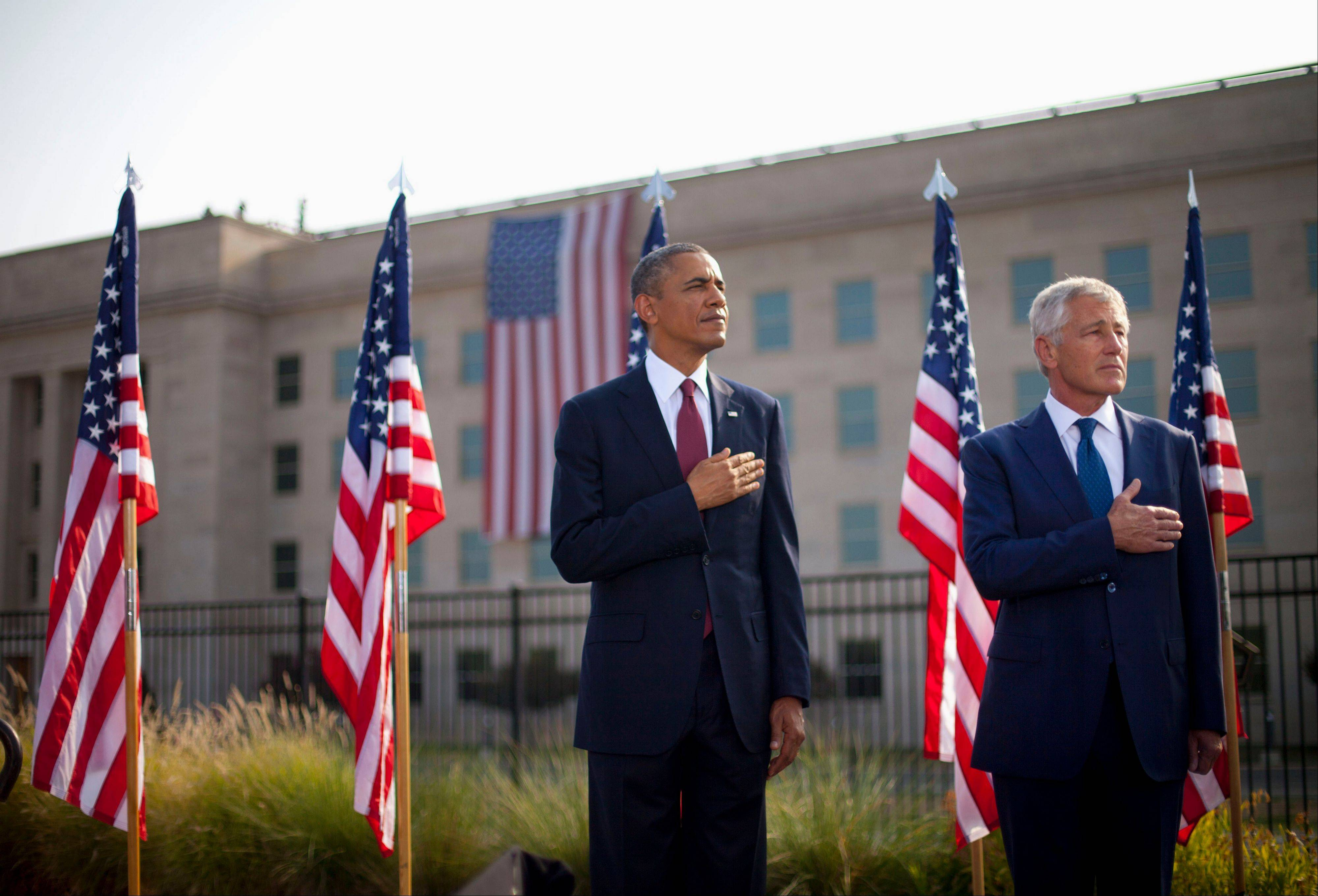 President Barack Obama and Defense Secretary Chuck Hagel hold their hands over their hearts during the playing of the national anthem, Wednesday, Sept. 11, 2013, at the Pentagon during a ceremony to mark the 12th anniversary of the 9/11 attacks.