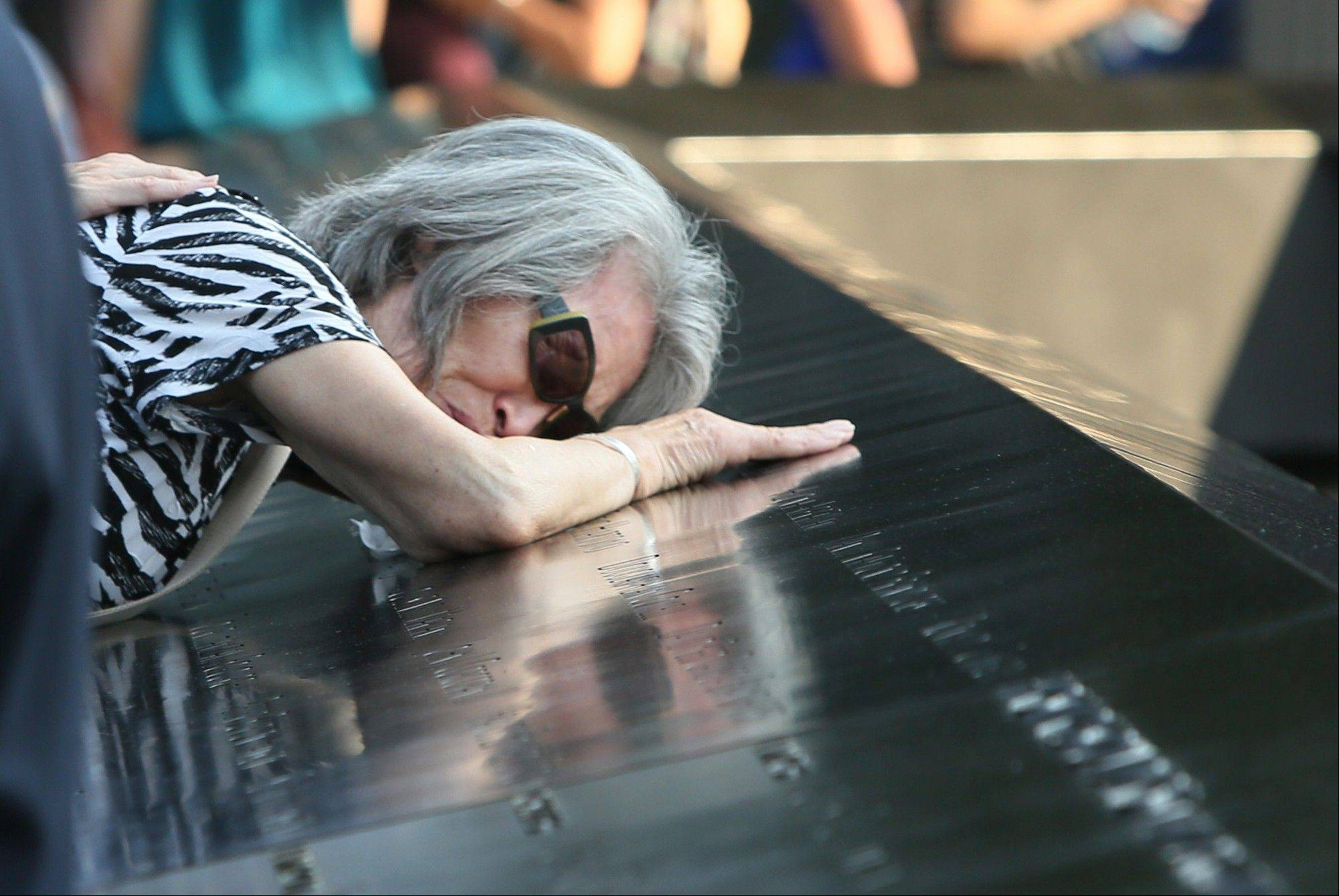 Mija Quigley, of Princeton Junction, N.J., embraces the name of her son, Patrick Quigley, during ceremonies marking the 12th anniversary of the 9/11 attacks on the World Trade Center in New York, Wednesday, Sept. 11, 2013. Patrick Quigley died aboard Flight 175 when it crashed into the south tower on 9/11.