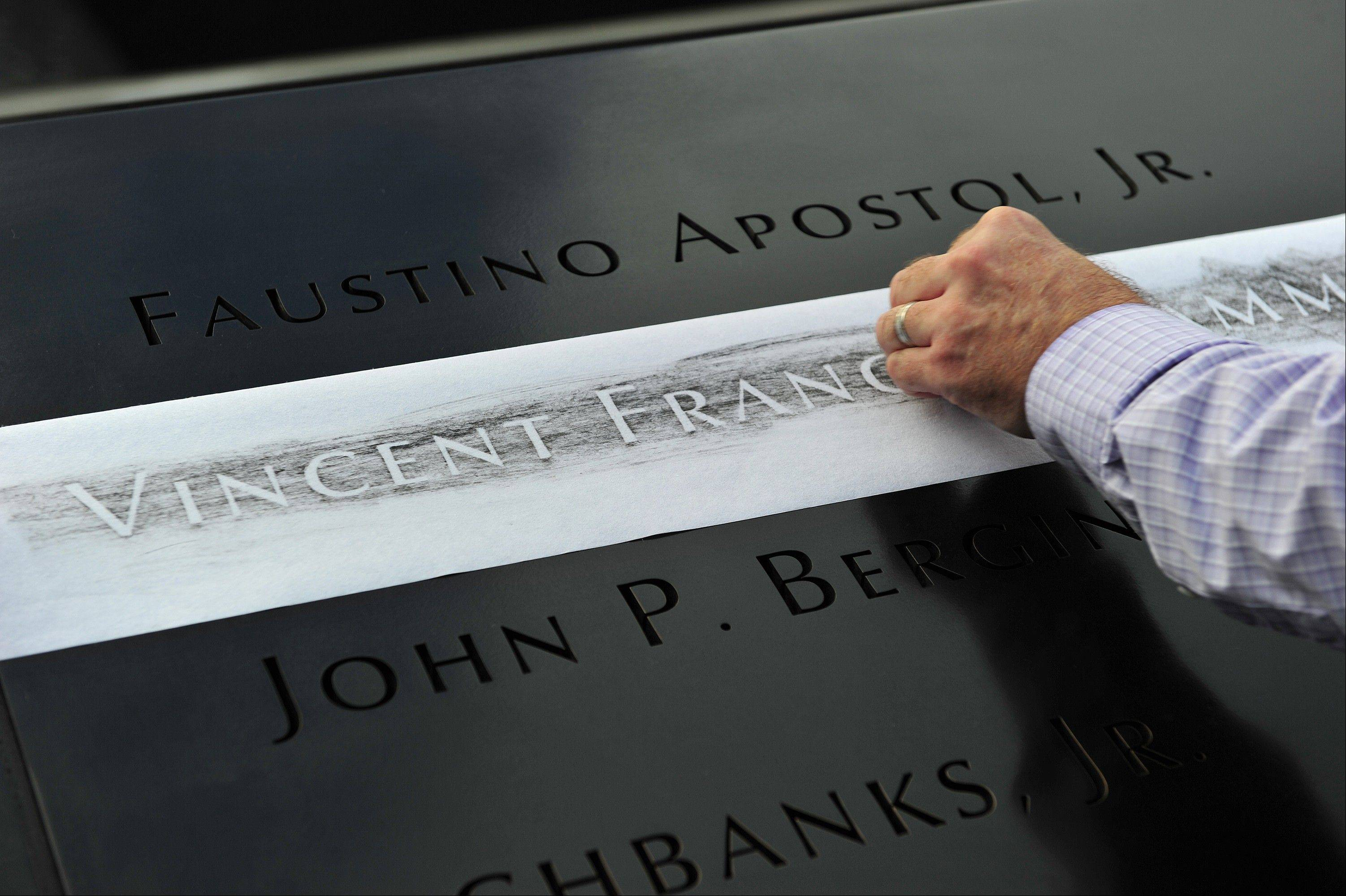 Ron Joy makes a rubbing of his friend's name, New York Fire Department firefighter Capt. Vincent Giammona, at the South reflecting pool at the Sept. 11 memorial on Wednesday, Sept. 11, 2013, during ceremonies marking the 12th anniversary of the Sept. 11 terrorist attacks in New York.