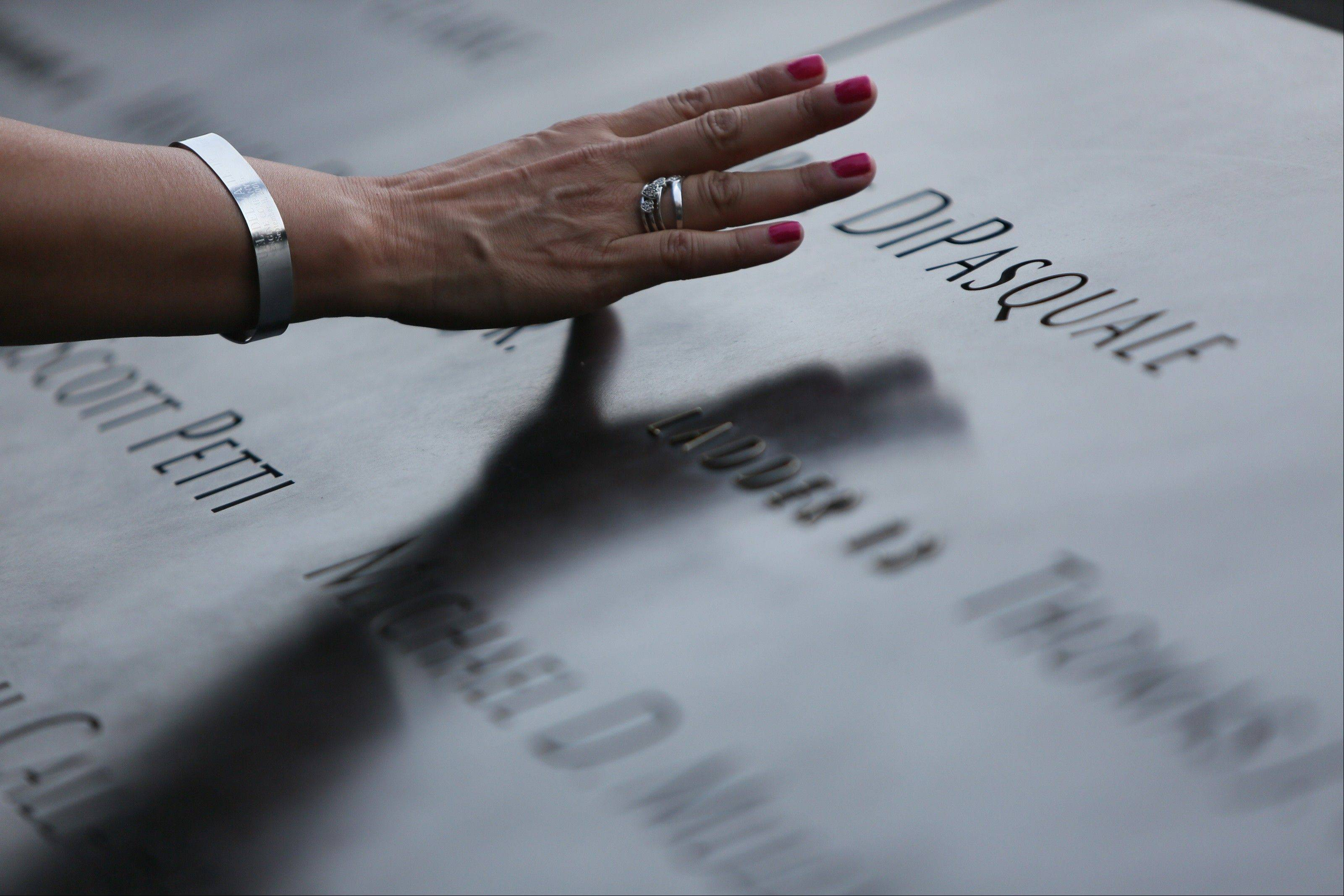 A woman touches the stone with names of the 9/11 victims at the Sept. 11 memorial during ceremonies marking the 12th anniversary of the attacks on the World Trade Center in New York, Wednesday, Sept. 11, 2013.