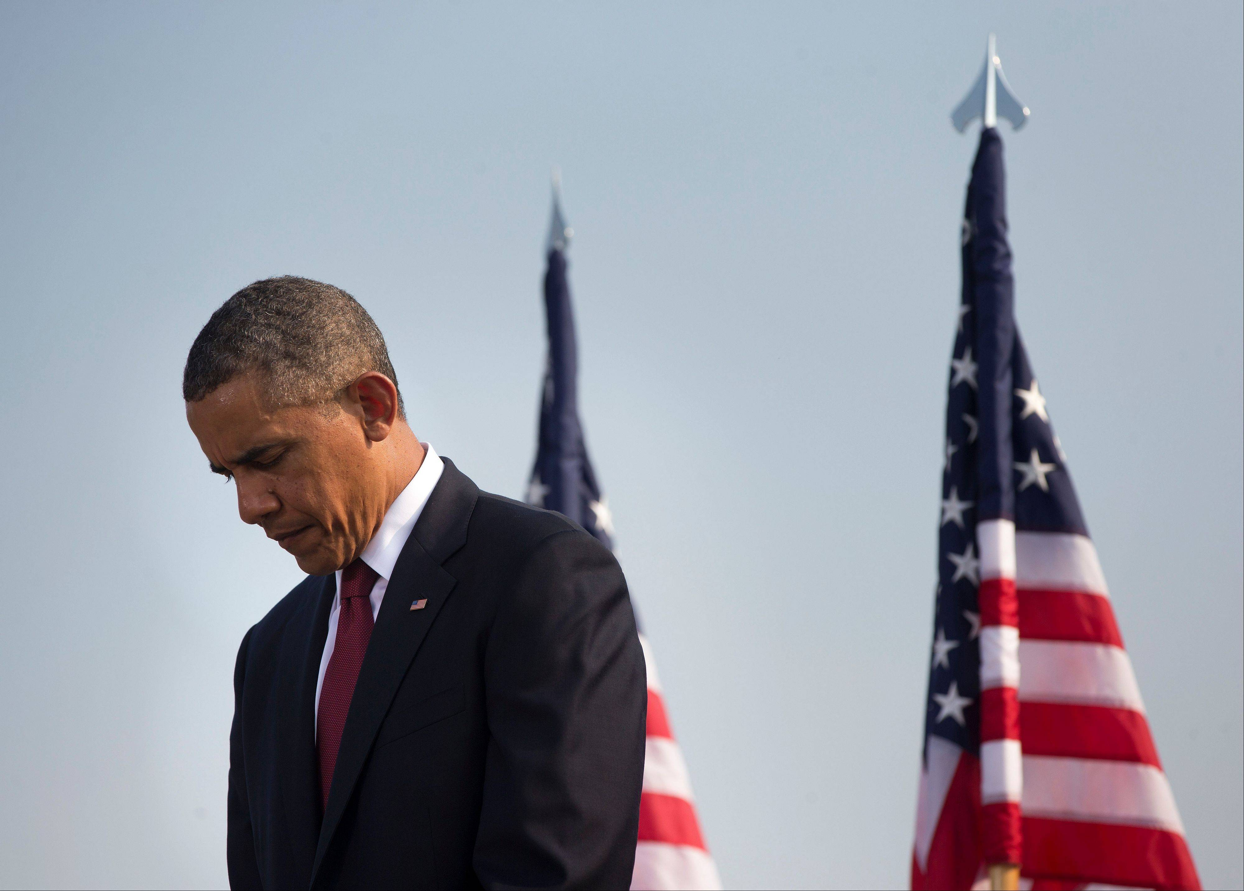 President Barack Obama lowers his head during a moment of silence at the Pentagon, Wednesday, Sept. 11, 2013, during a ceremony to mark the 12th anniversary of the 9/11 attacks.