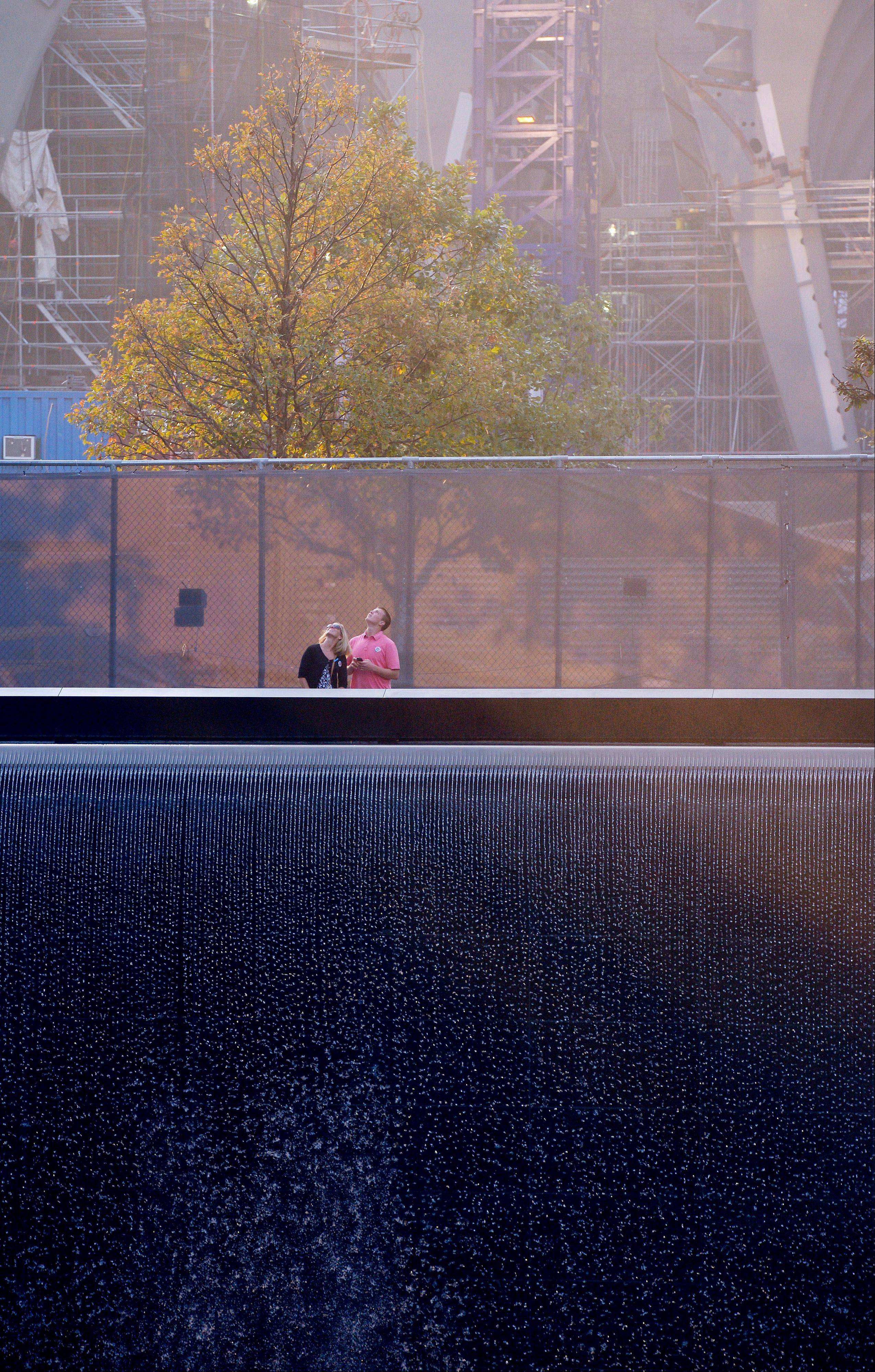 Two people stand at the edge of the north reflecting pool at the Sept. 11 memorial during a ceremony marking the 12th anniversary of the 9/11 attacks on the World Trade Center, in New York, Wednesday, Sept. 11, 2013.