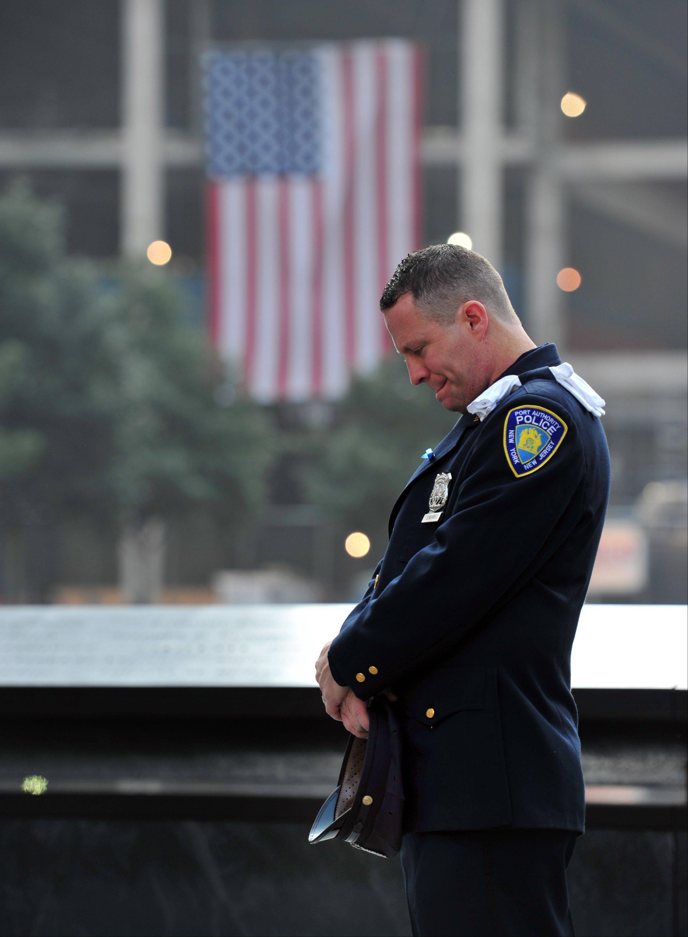 Daniel Henry, a Port Authority of New York/New Jersey police officer, pauses during a moment of silence at 9:01 a.m. at the south reflecting pool at the Sept. 11 memorial on Wednesday, Sept. 11, 2013, during ceremonies marking the 12th anniversary of the 9/11 terrorist attacks in New York.