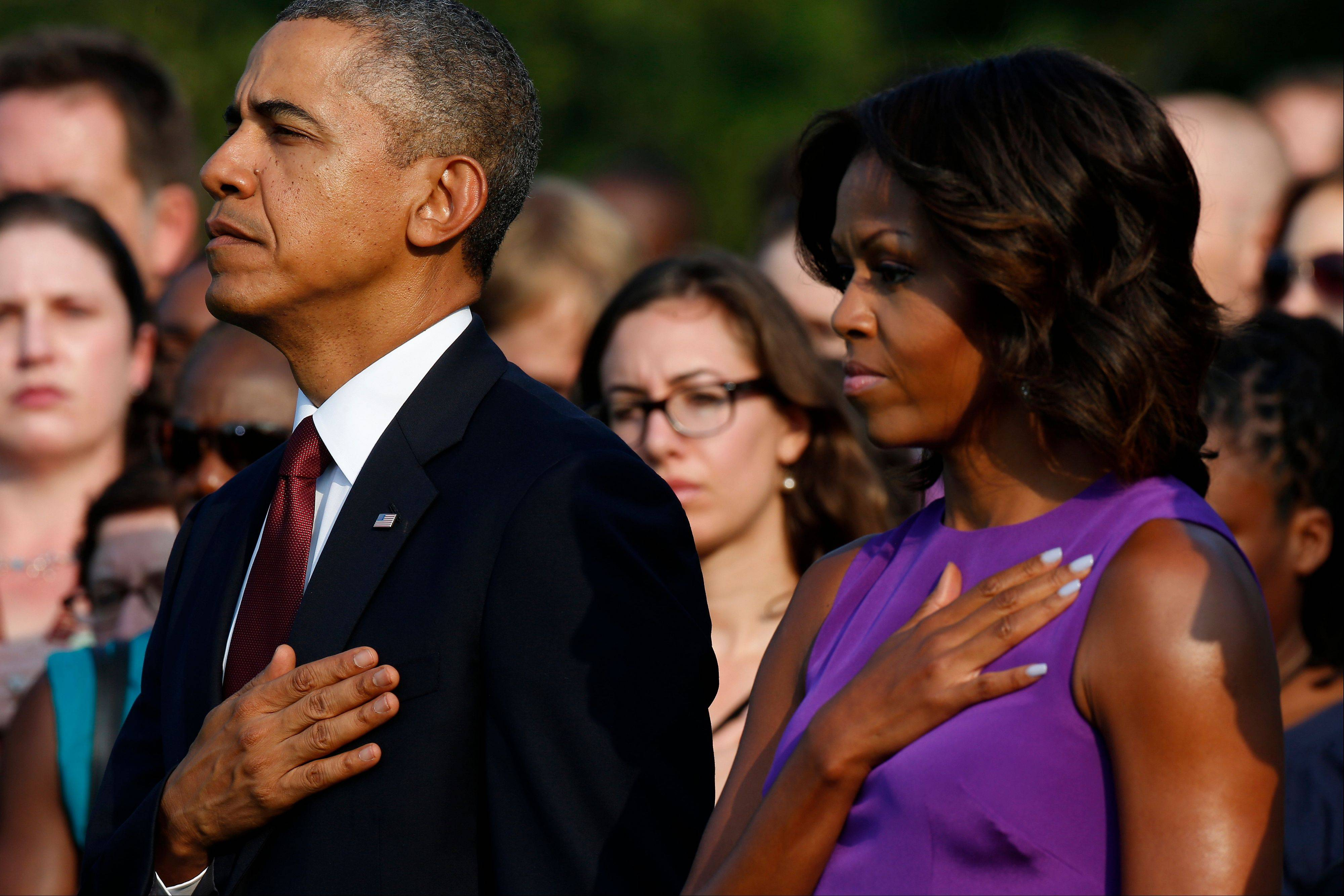 "President Barack Obama and first lady Michelle Obama put their hands on their hearts during the playing of ""Taps"" as they stand on the South Lawn of the White House in Washington, Wednesday, Sept. 11, 2013, to mark the 12th anniversary of the September 11 terror attacks."