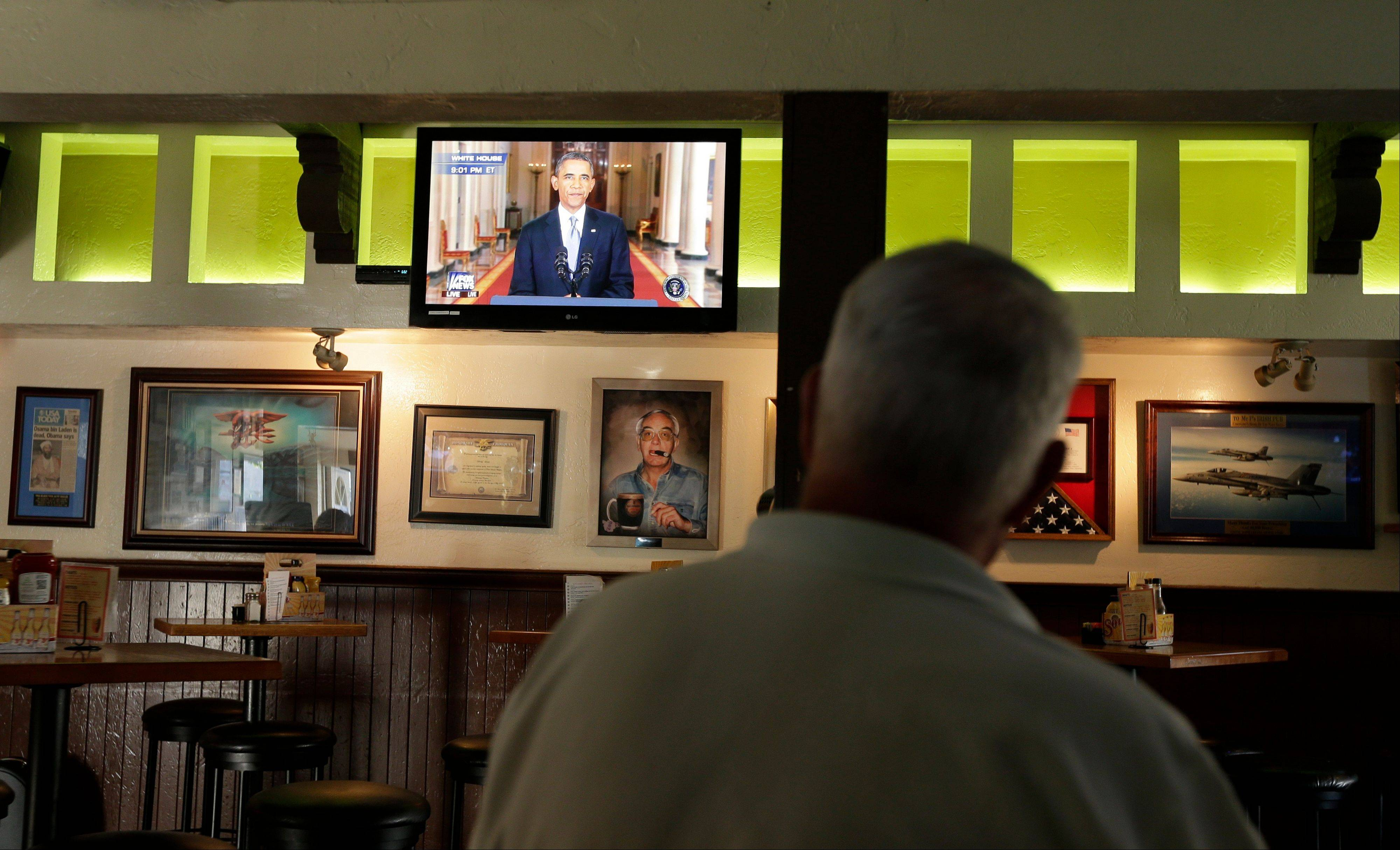 John Merry watches President Barack Obama deliver a speech about relations with Syria from McP's Pub, Tuesday, Sept. 10, 2013, in Coronado, Calif.