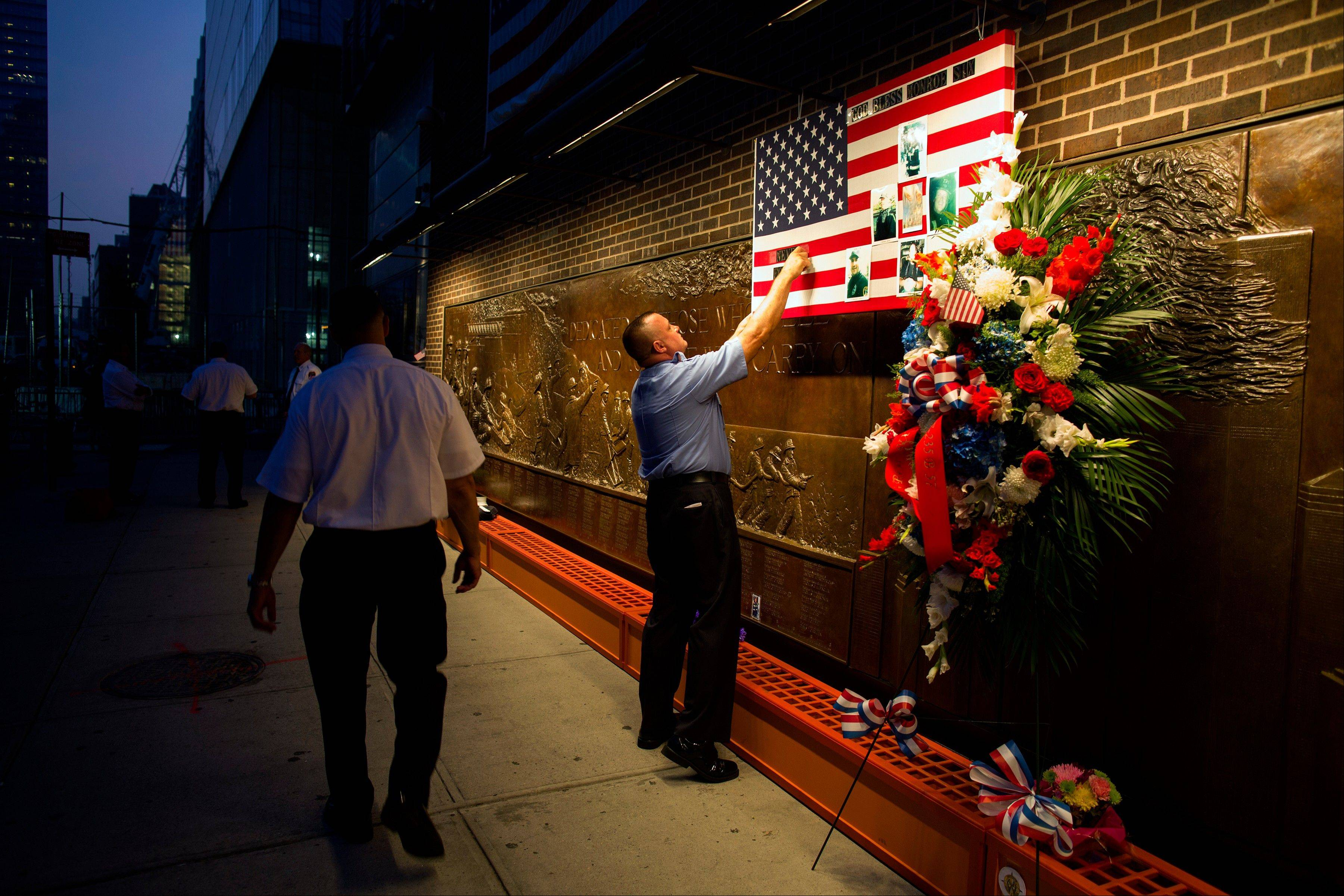 FDNY Firefighter Mike Bellantoni of New York prepares a memento at the Firefighter's Memorial adjacent to the World Trade Center Wednesday, Sept. 11, 2013 before the start of the official ceremonies at the 9/11 Memorial nearby.