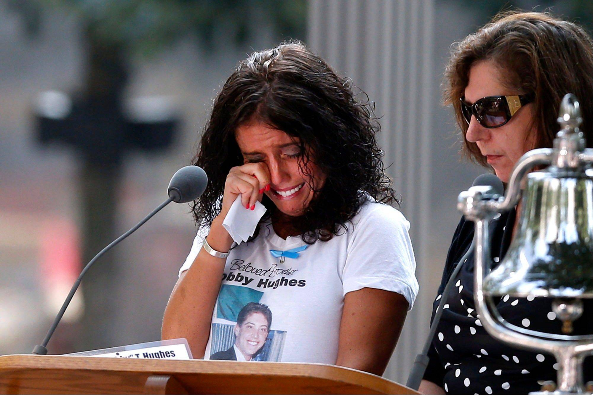 A woman wipers her eyes after reading the name of her brother, Bobby Hughes, as friends and relatives of the victims of the 9/11 terrorist attacks gather at the National September 11 Memorial at the World Trade Center site Wednesday for a ceremony marking the 12th anniversary of the attacks.