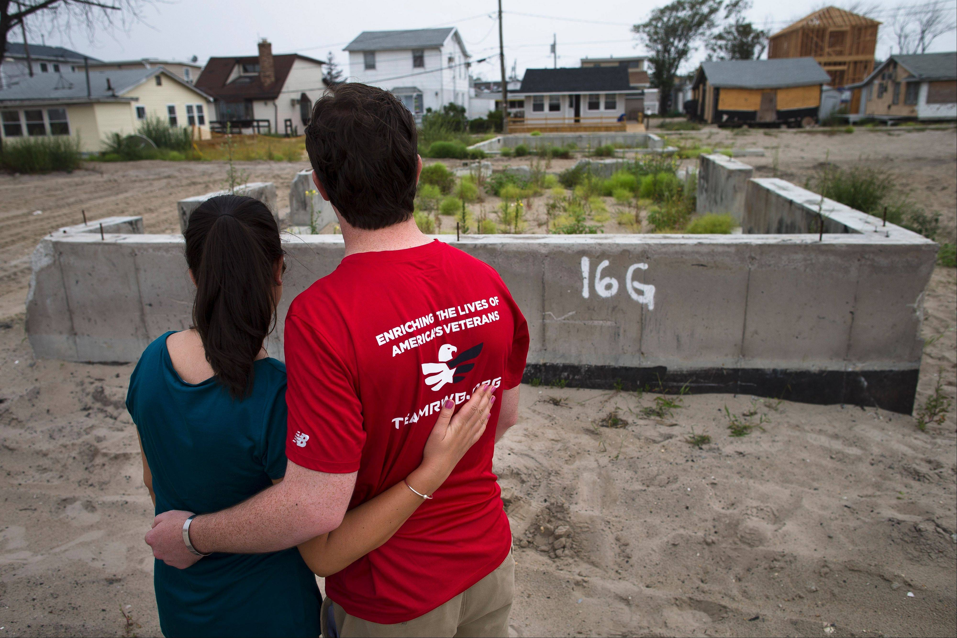 Joe Quinn and his wife, Melanie, visit the remains of his parents' home that was destroyed by Superstorm Sandy in the Breezy Point neighborhood of New York's Queens borough. Joe Quinn, whose older brother Jimmy was killed on the 104th floor of the World Trade Center's Tower One on Sept. 11, 2001, lost treasured pictures and handwritten letters from his brother that were among 12 boxes of mementos that were lost in the house when Superstorm Sandy struck the Queens community last October.