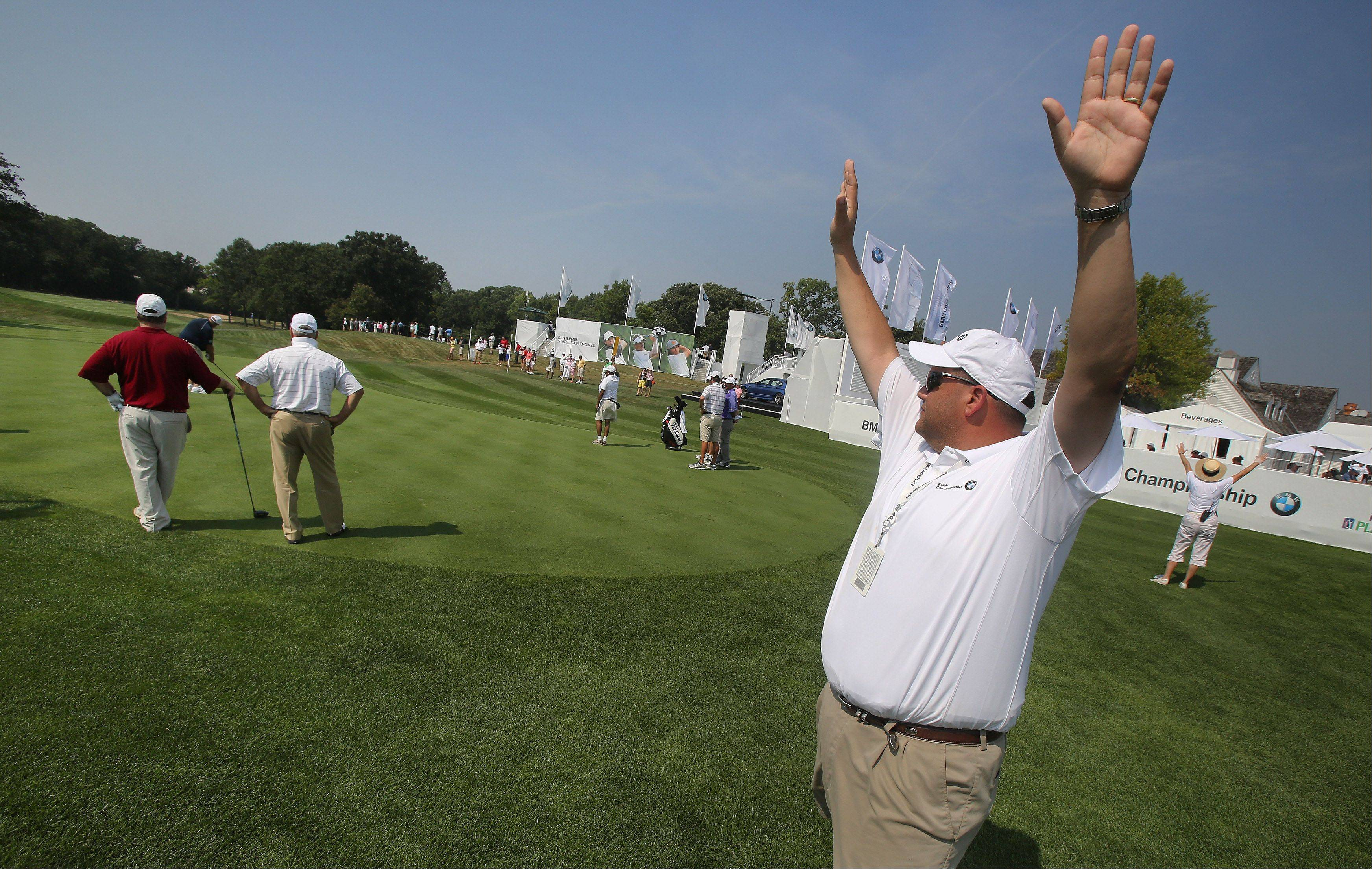 Volunteer Sean Finnegan of Lindenhurst holds up his hands to keep the crowd quiet on the first hole as golfers tee off for a practice round at the BMW Championship at Conway Farms Golf Club in Lake Forest.
