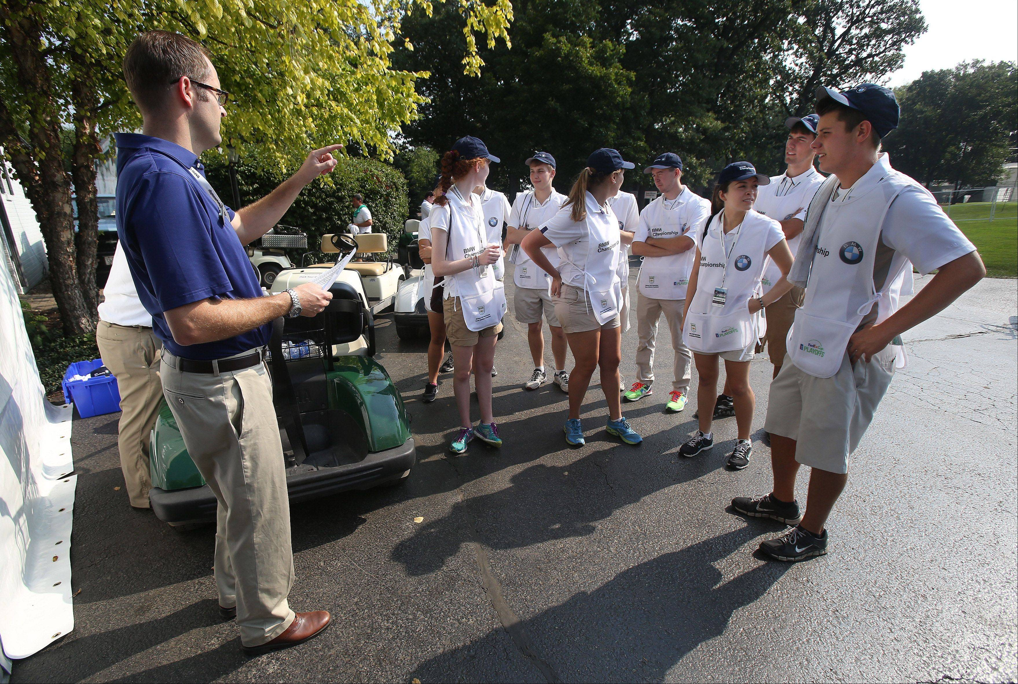 Brian Shell, Western Golf Association education director, talks to the volunteer caddies, all Evans Scholars, on the first day of the BMW Championship at Conway Farms Golf Club in Lake Forest.