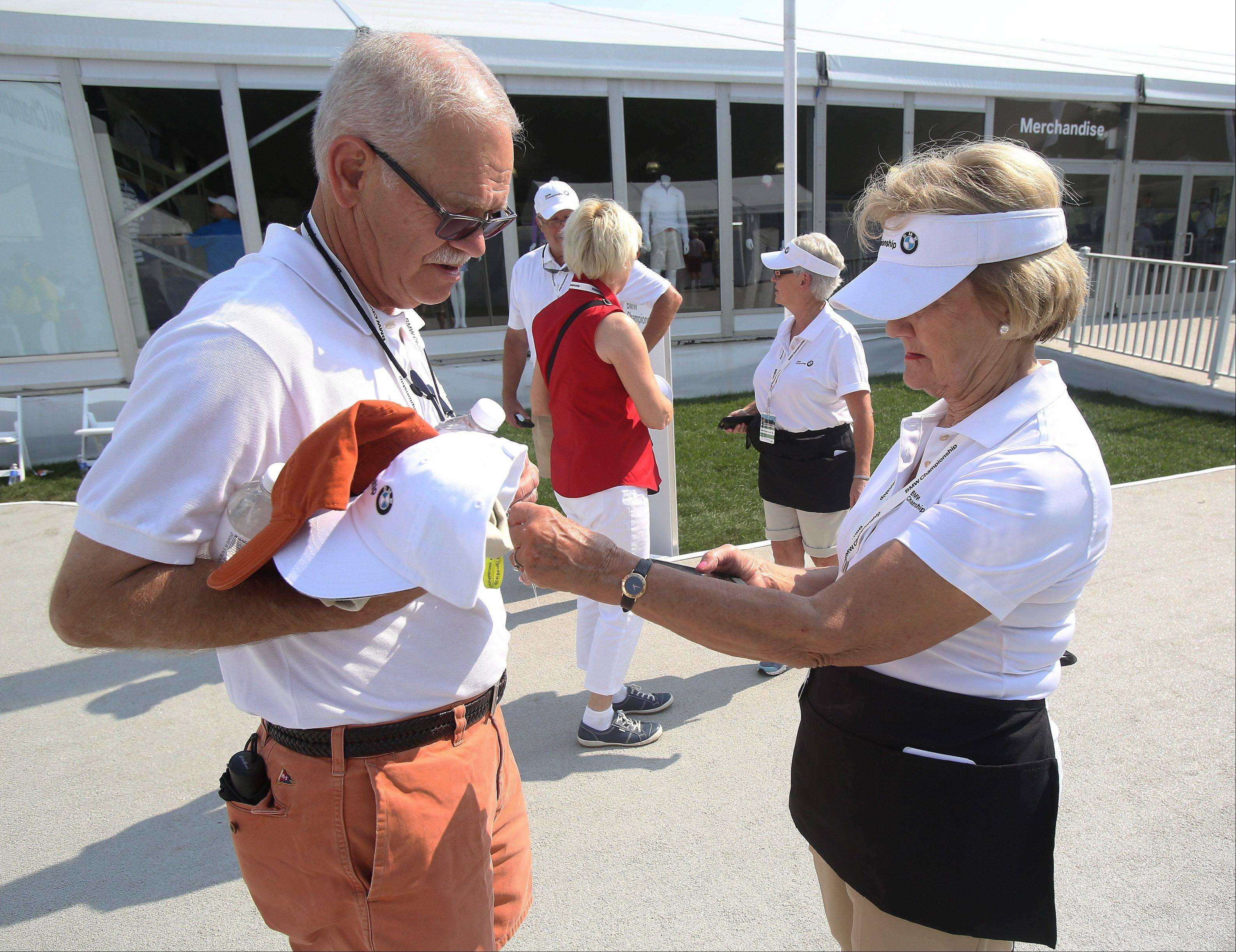 Volunteer Sharon Collias, right, scans tickets as visitors pass through the front gate at the BMW Championship Monday at Conway Farms Golf Club in Lake Forest.
