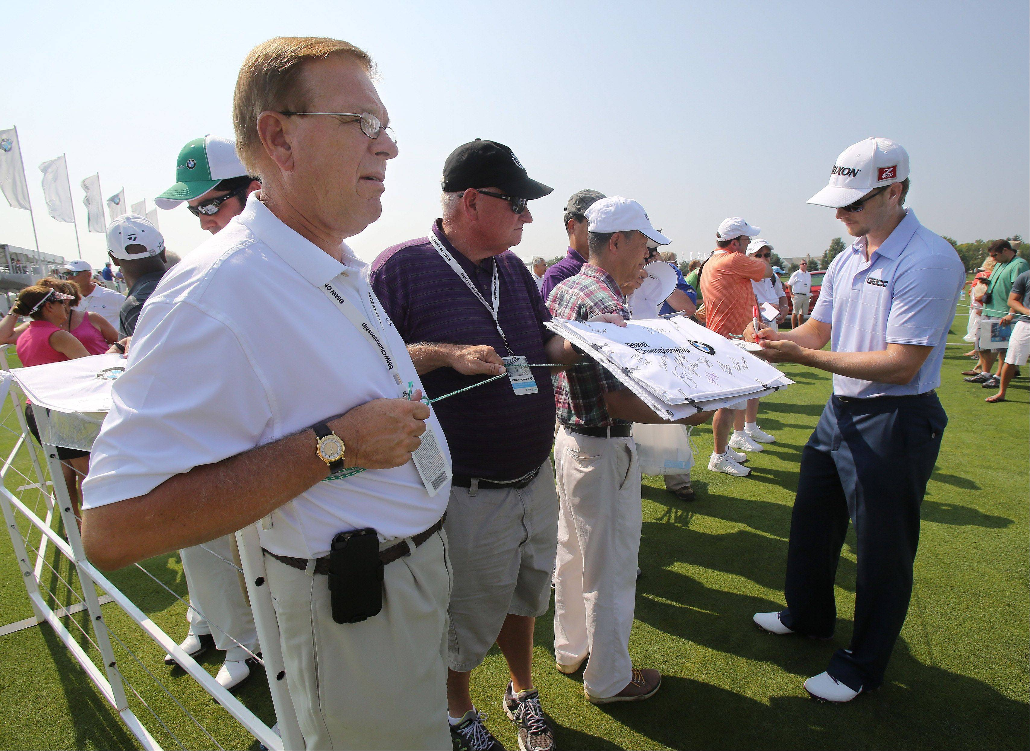 Volunteer C.M. Bottema of Indianapolis, left, holds the line as golfer Chris Stroud signs autographs at the BMW Championship at Conway Farms Golf Club in Lake Forest. Volunteers are a crucial part of tournament operations, organizers say.