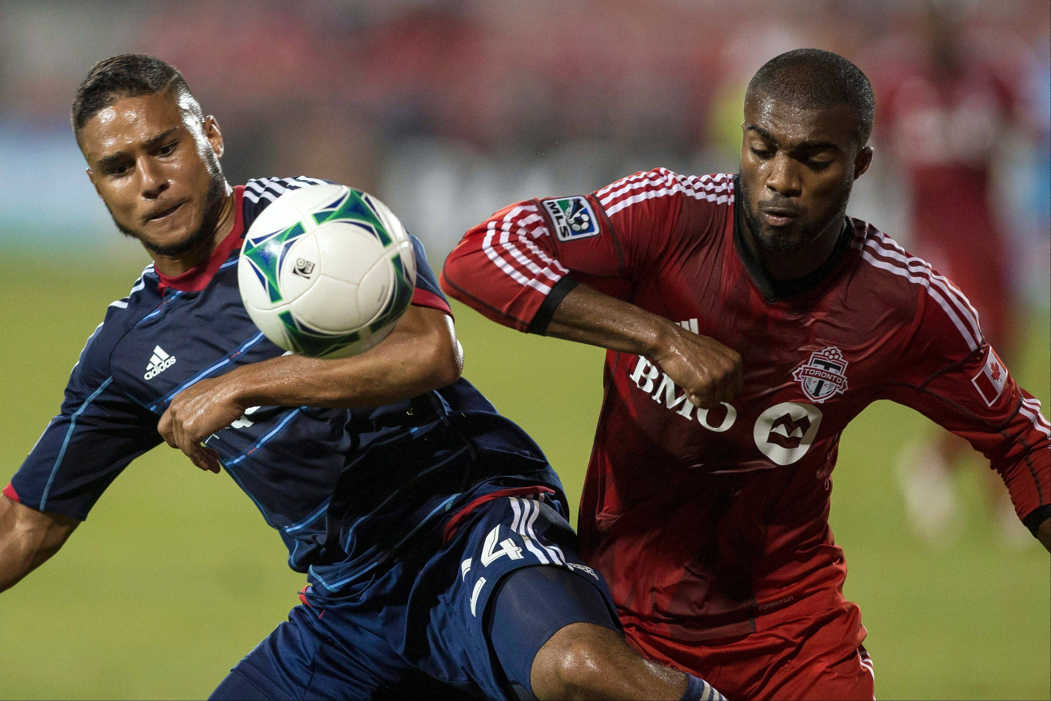 Toronto FC's Ashtone Morgan, right, and Chicago Fire's Quincy Amarikwa battle for control of the ball during their 1-1 game Wednesday night.