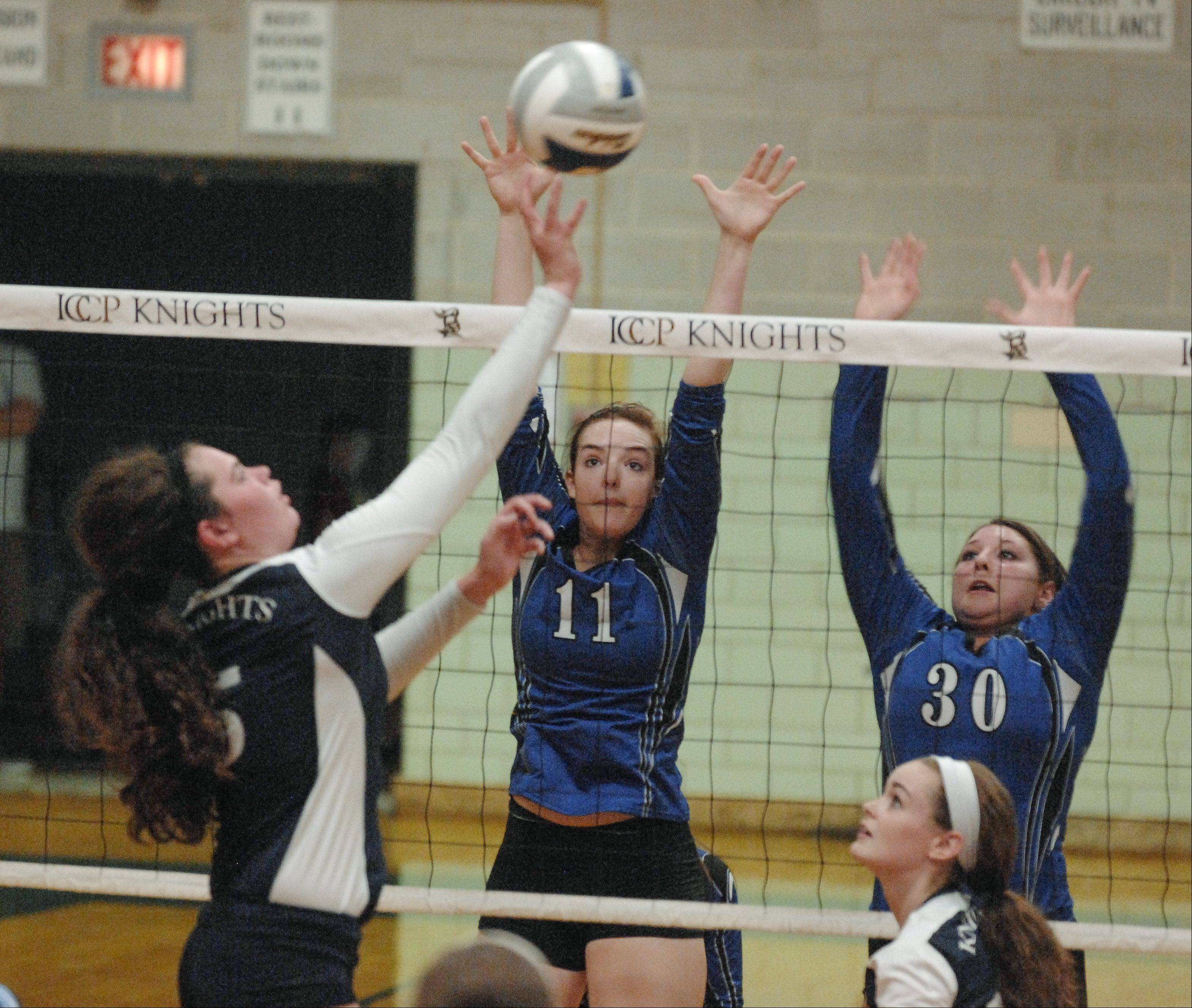 Rory Manion of IC Catholic Prep hits one past Becca Shearer and Kristin Acciavatti of St. Francis during girls volleyball in Elmhurst, Wednesday.