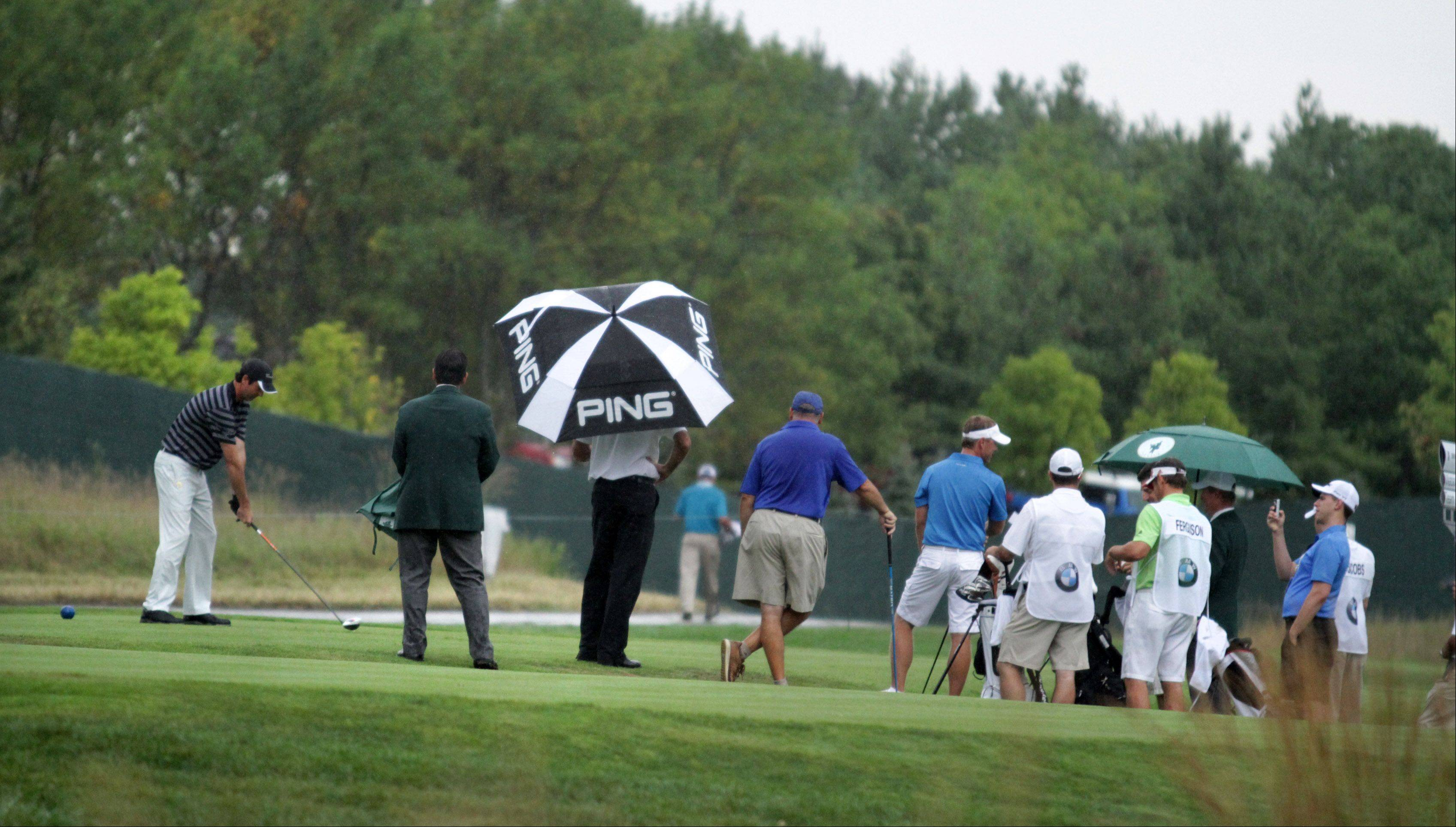 Bubba Watson holds an umbrella during a brief ran as one of his amateur teammates tees off on the tenth hole in the Gardner Heidrick Pro-Am tournament.