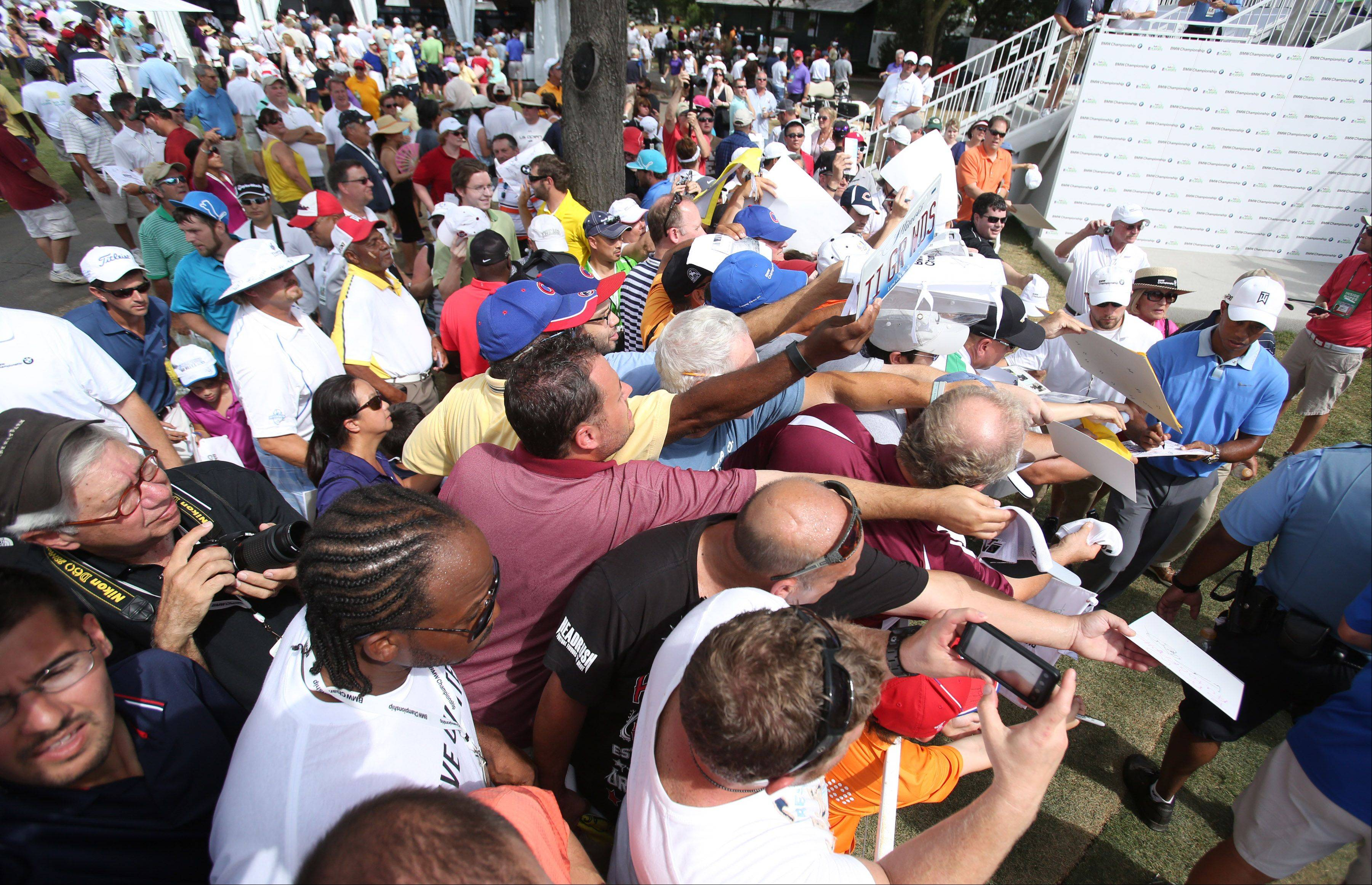 Hundreds of fans try to get Tiger Woods' autograph after a press conference.