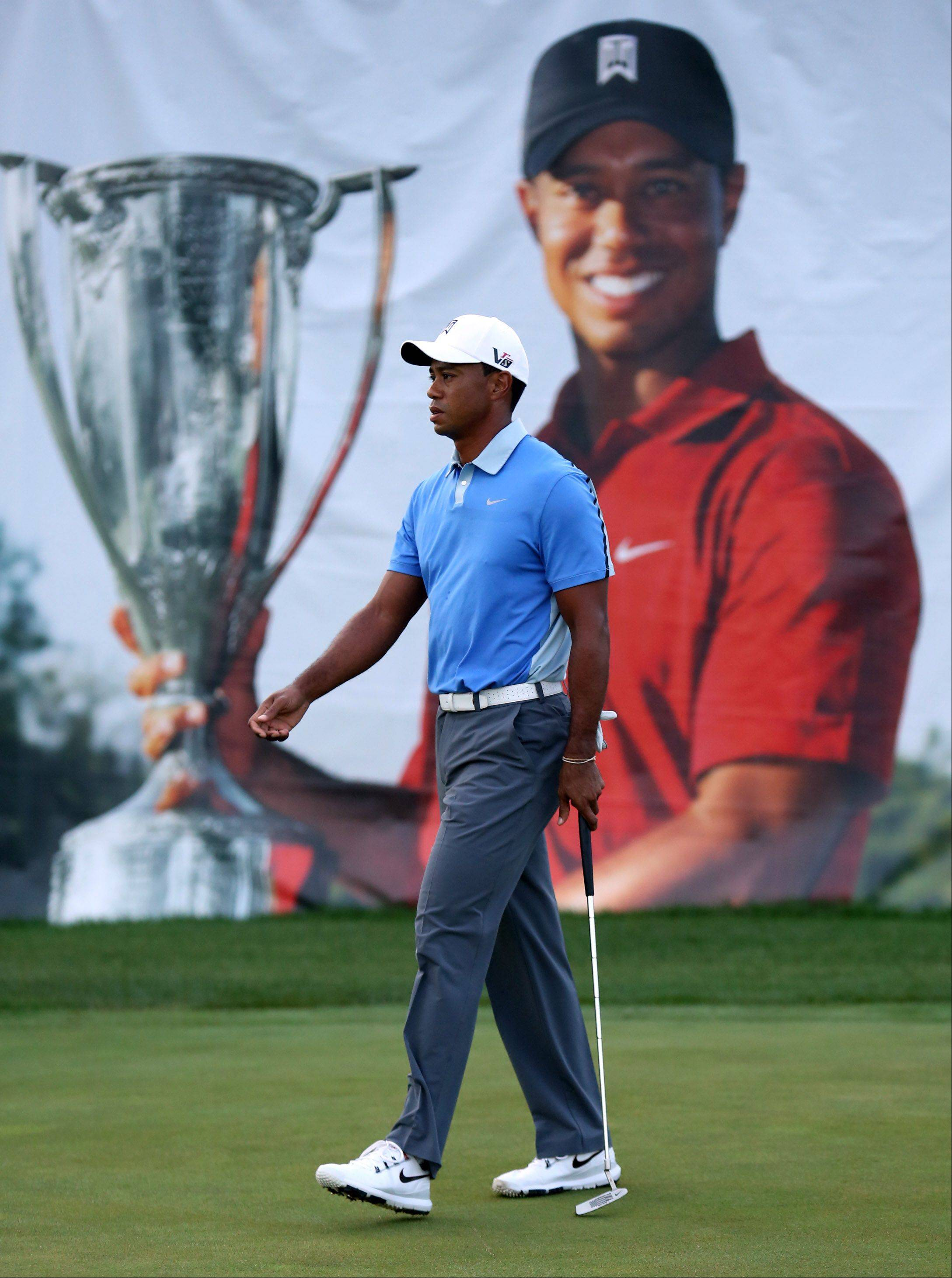 Tiger Woods walks past the practice driving range.