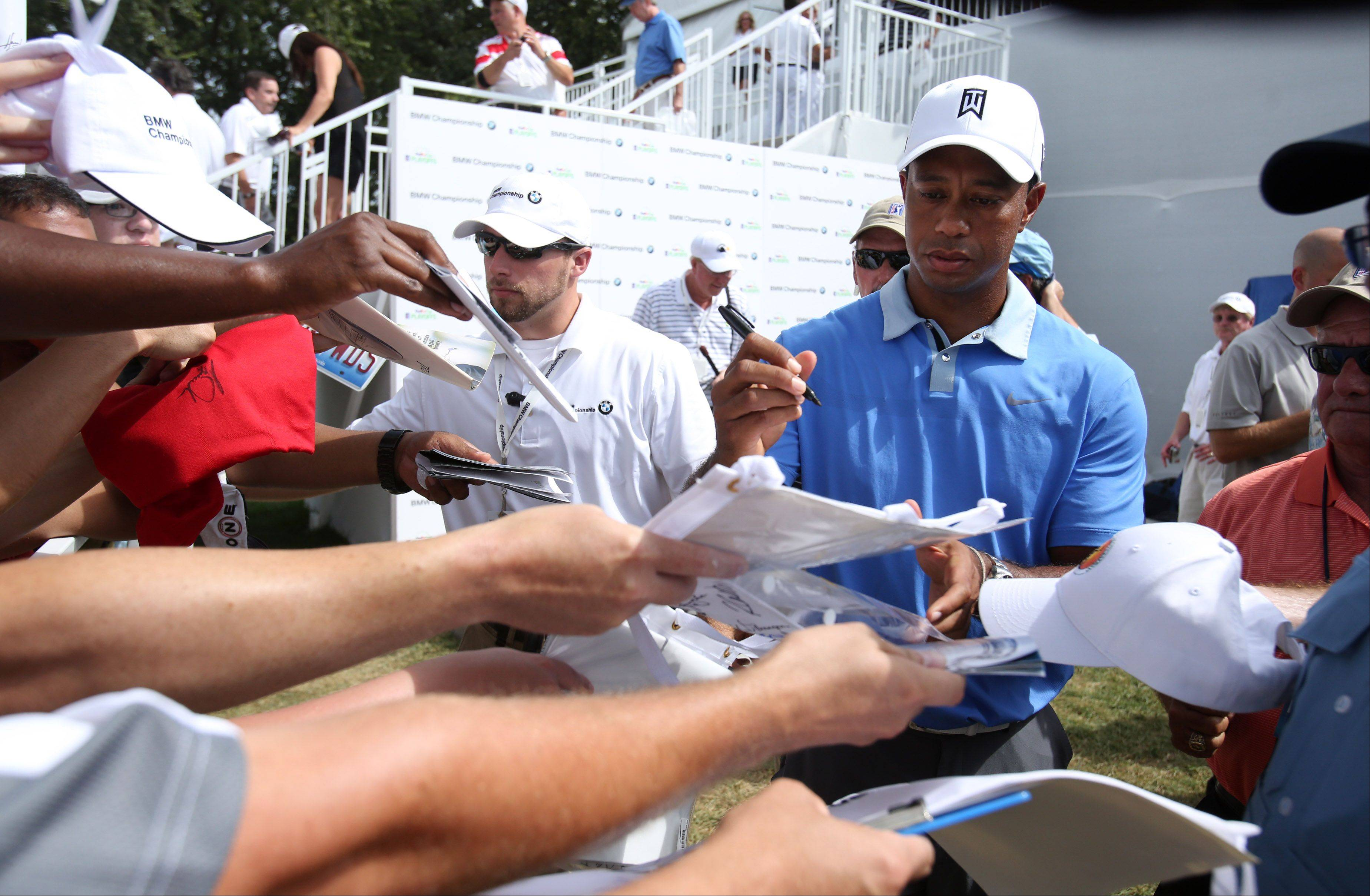 Fans try to get Tiger Woods' autograph.