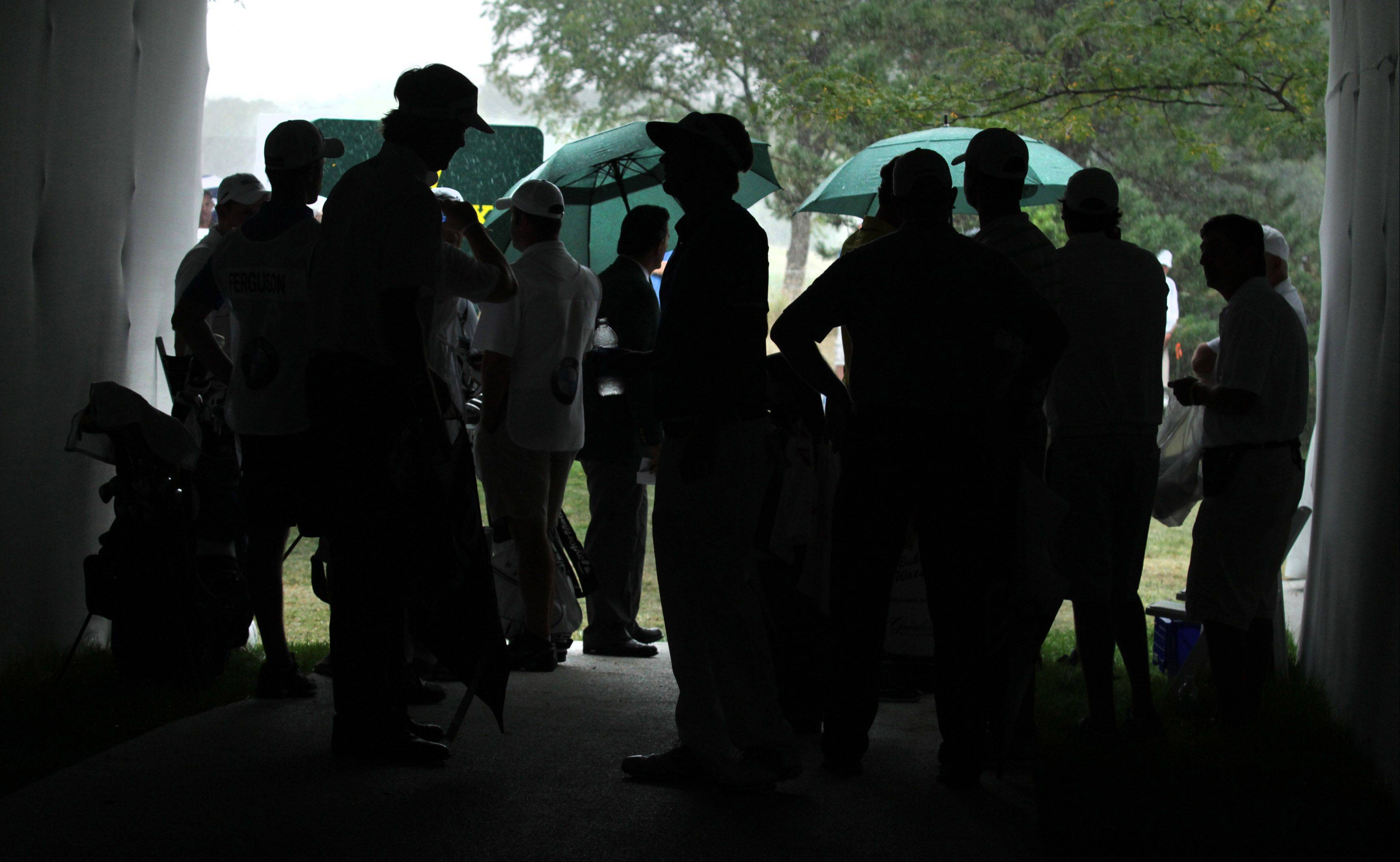 Golfers and caddies wait in a tunnel during a brief rain storm at the tenth hole.