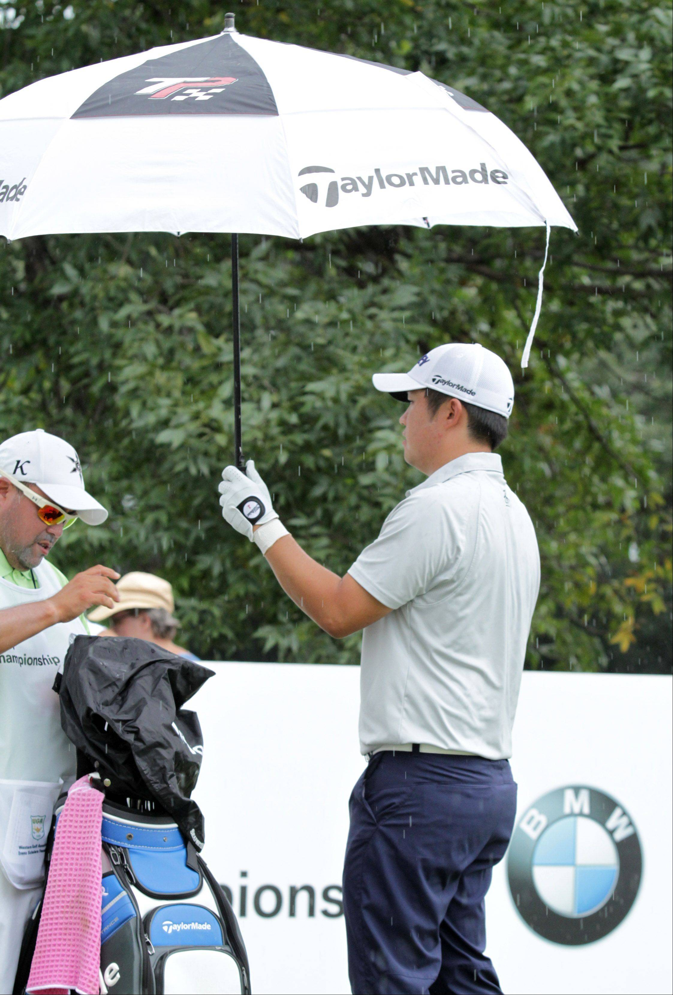 John Huh holds an umbrella for his caddy on the tenth hole.