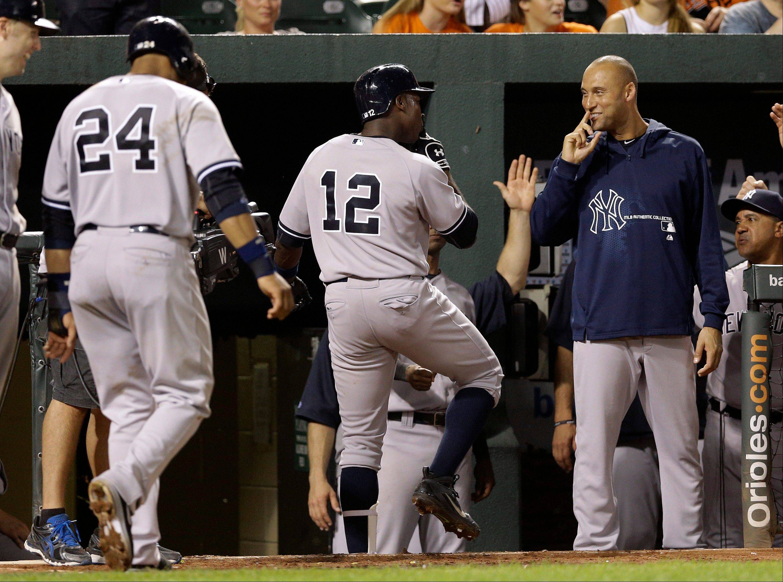 New York Yankees' Alfonso Soriano (12) and Derek Jeter, right, gestures after Soriano drove in teammate Robinson Cano (24) on a home run in the eighth inning of a baseball game against the Baltimore Orioles, Tuesday, Sept. 10, 2013, in Baltimore. New York won 7-5.