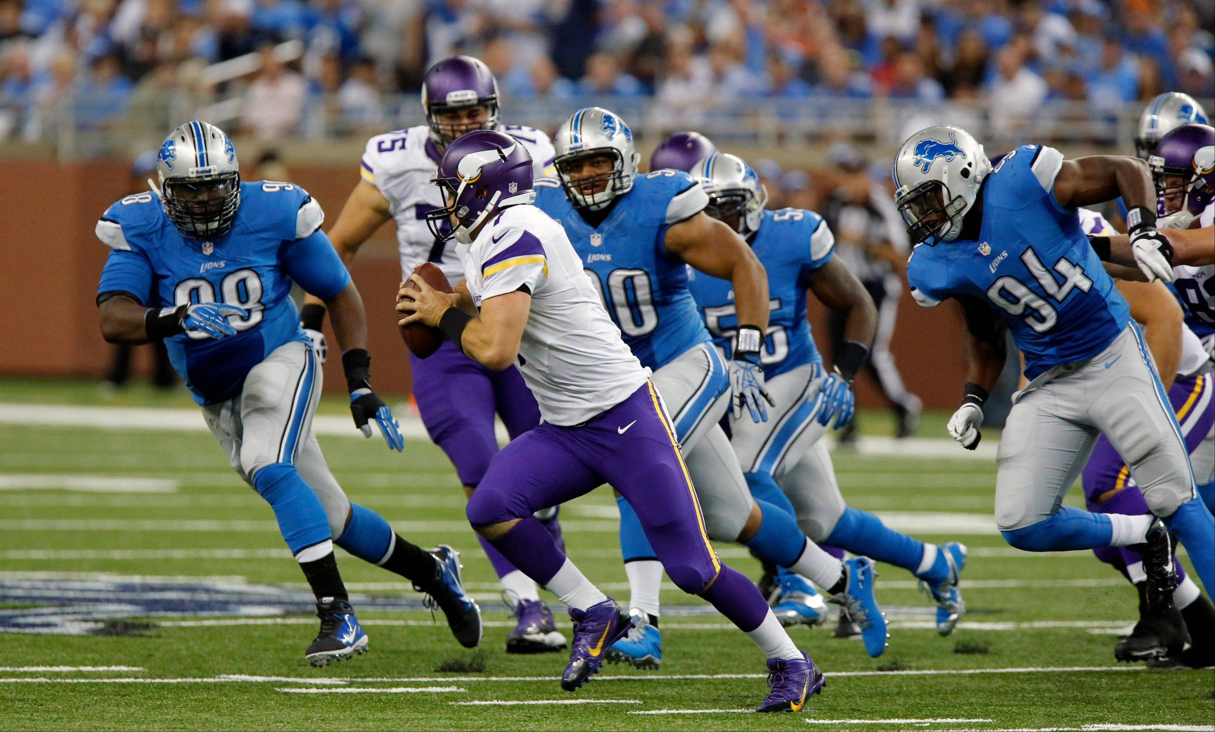 Minnesota Vikings quarterback Christian Ponder (7) is chased by Detroit Lions defensive tackle Nick Fairley (98), defensive tackle Ndamukong Suh (90) and defensive end Ezekiel Ansah (94) during the fourth quarter of an NFL football game at Ford Field in Detroit, Sunday, Sept. 8, 2013.