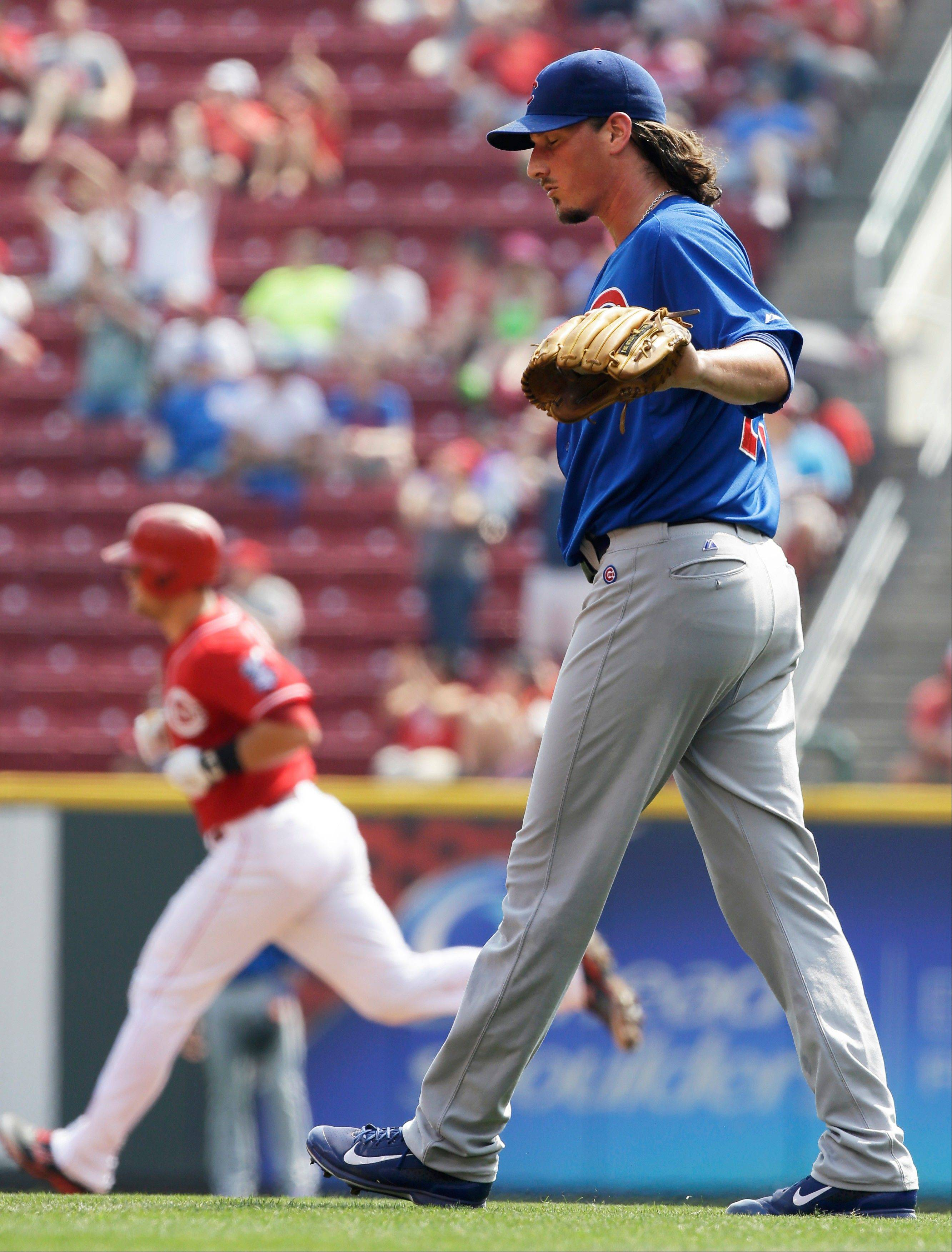 Cubs starting pitcher Jeff Samardzija walks behind the mound Wednesday after giving up a solo home run to Cincinnati Reds' Devin Mesoraco, rounding the bases at left, in the fourth inning in Cincinnati.