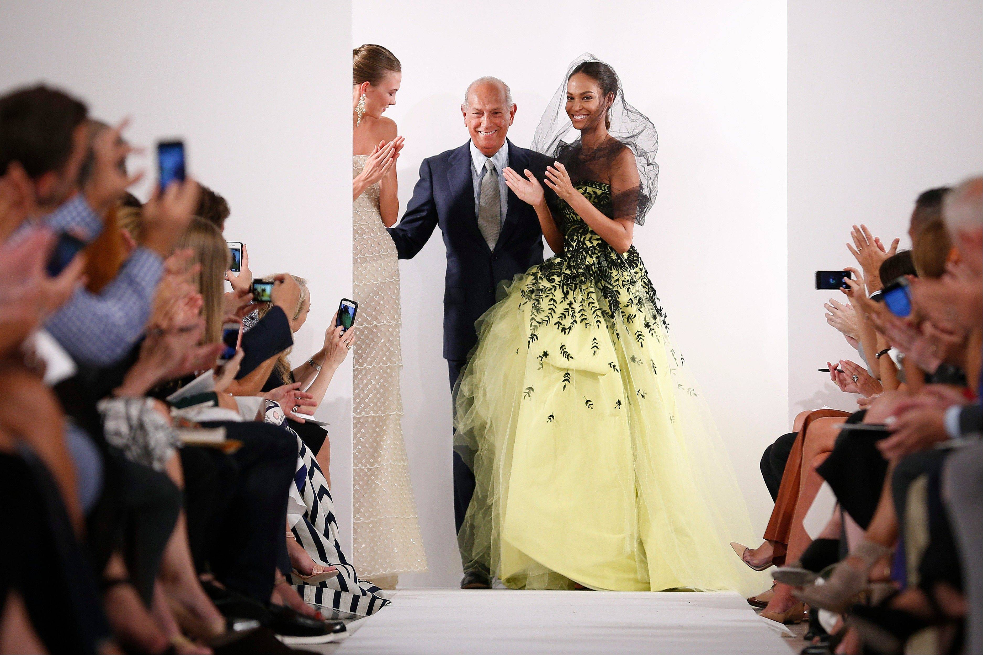 Designer Oscar de la Renta, center, greets the audience after his Spring 2014 collection was modeled during Fashion Week in New York.