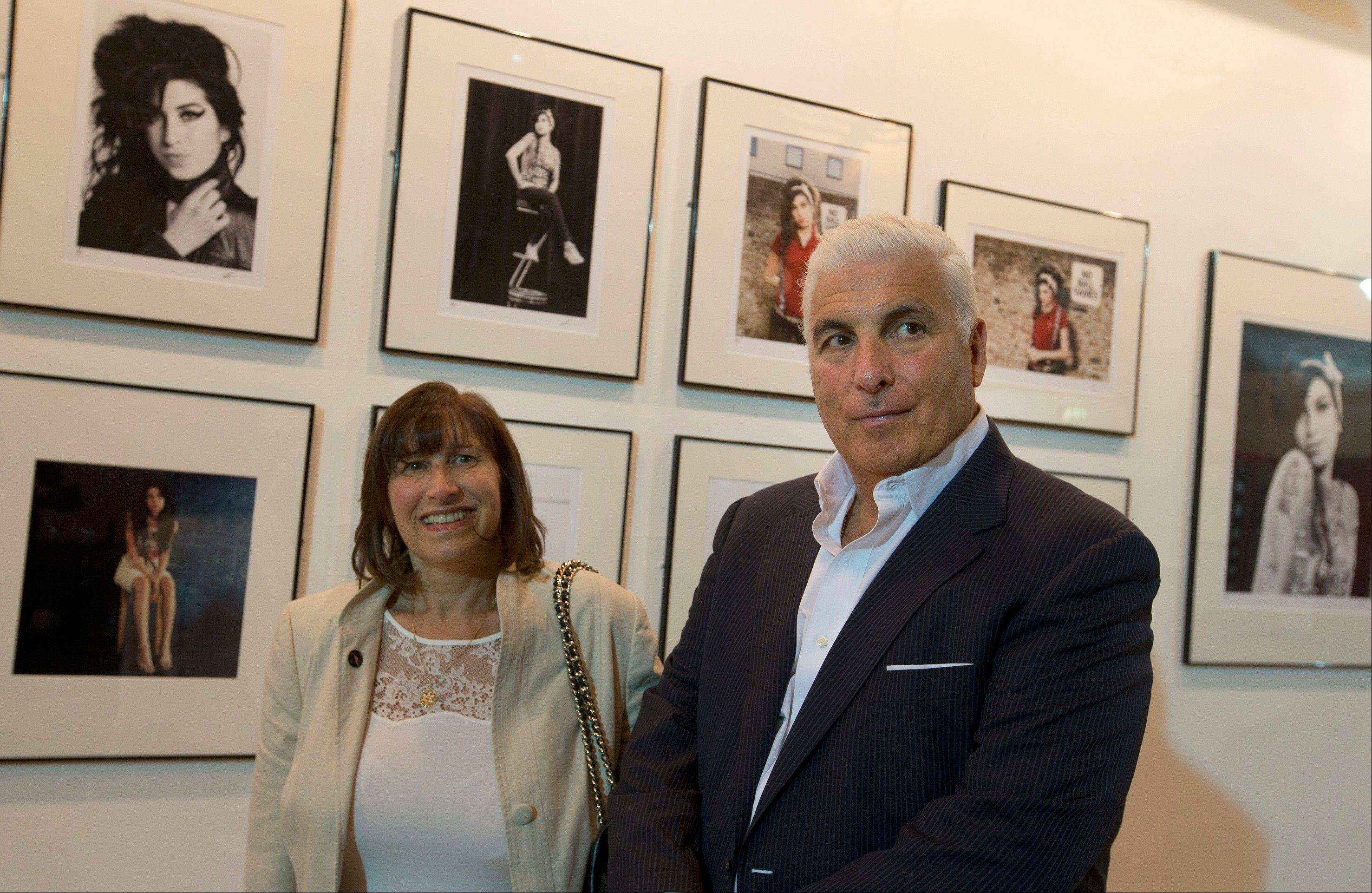Janice and Mitch Winehouse mother and father of the late British singer Amy in front of portraits of their daughter at the Proud gallery in Camden, London.