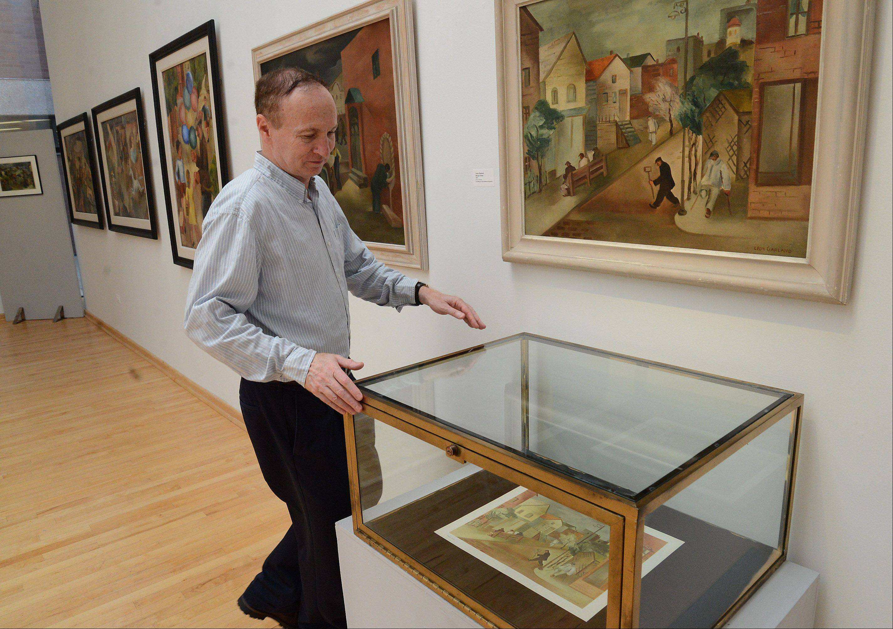 "Curator Nathan Harpaz takes a closer look of a print made from the original Leon Garland painting hanging above it, called ""Morgan Street."" Garland painted it in 1941."