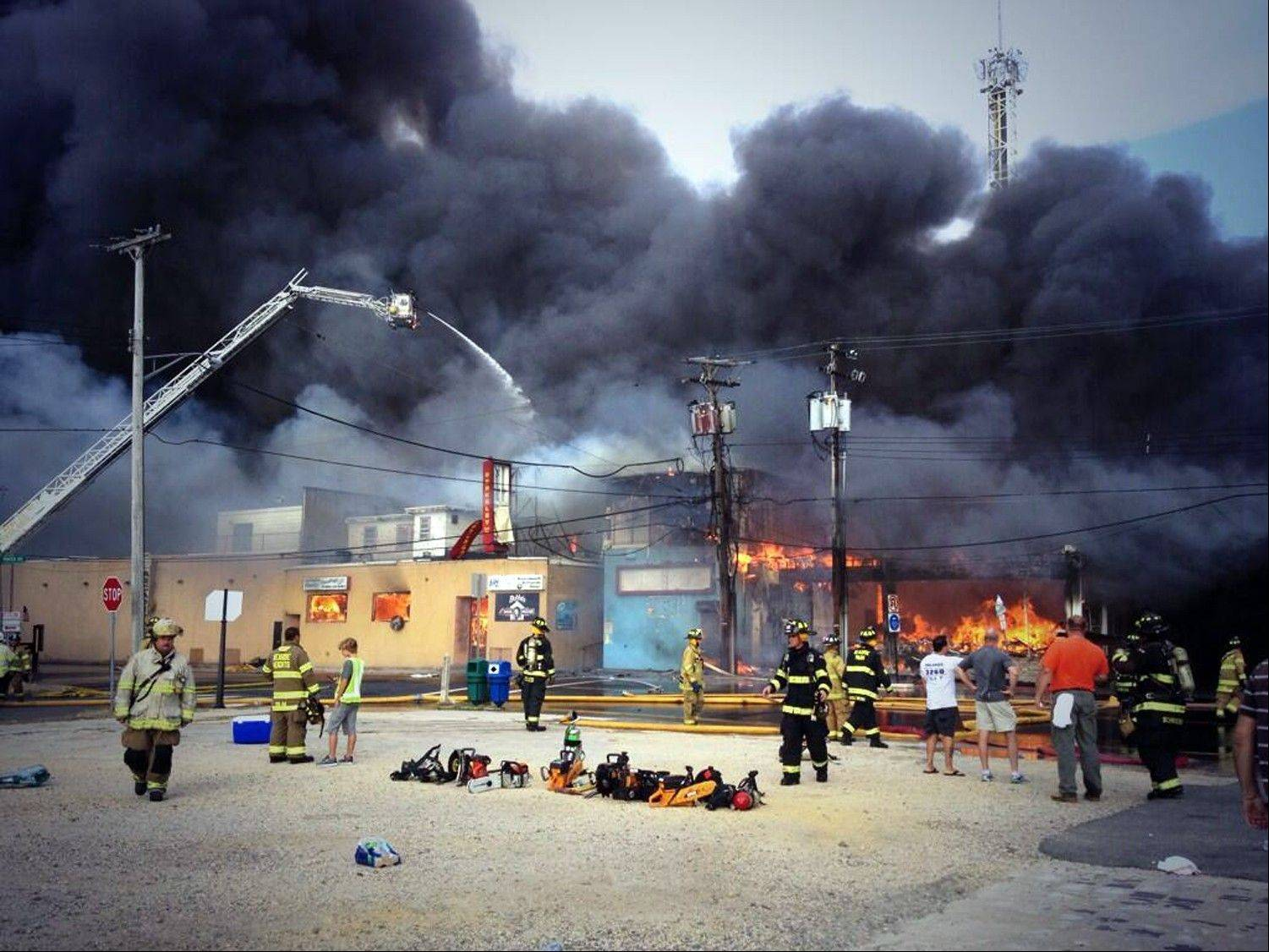 Firefighters battle a raging fire on the boardwalk in Seaside Heights, N.J., that apparently started in an ice cream shop and has spread several blocks down Thursday. The boardwalk was damaged in Superstorm Sandy and was being repaired.
