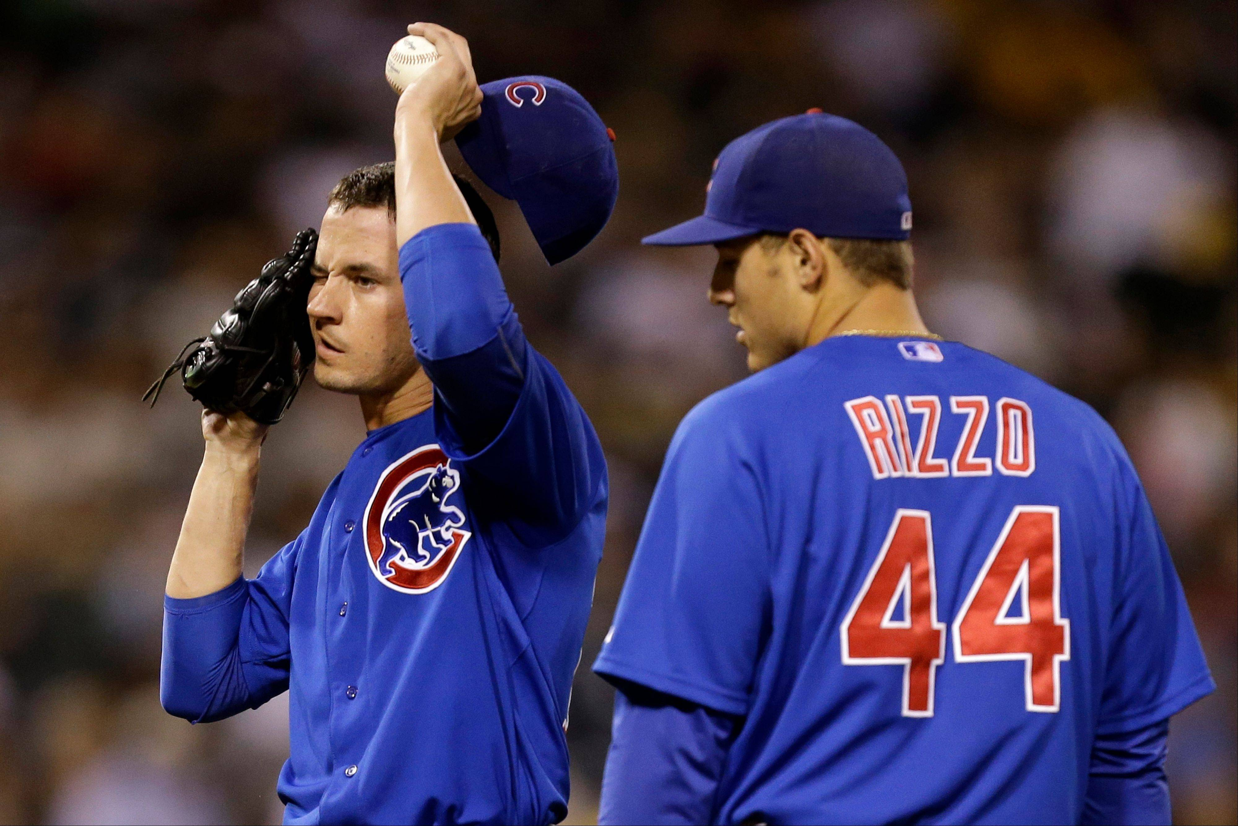Cubs starting pitcher Chris Rusin is visited on the mound by first baseman Anthony Rizzo after giving up an RBI single to Pittsburgh's Pedro Alvarez in the fourth inning Thursday night.