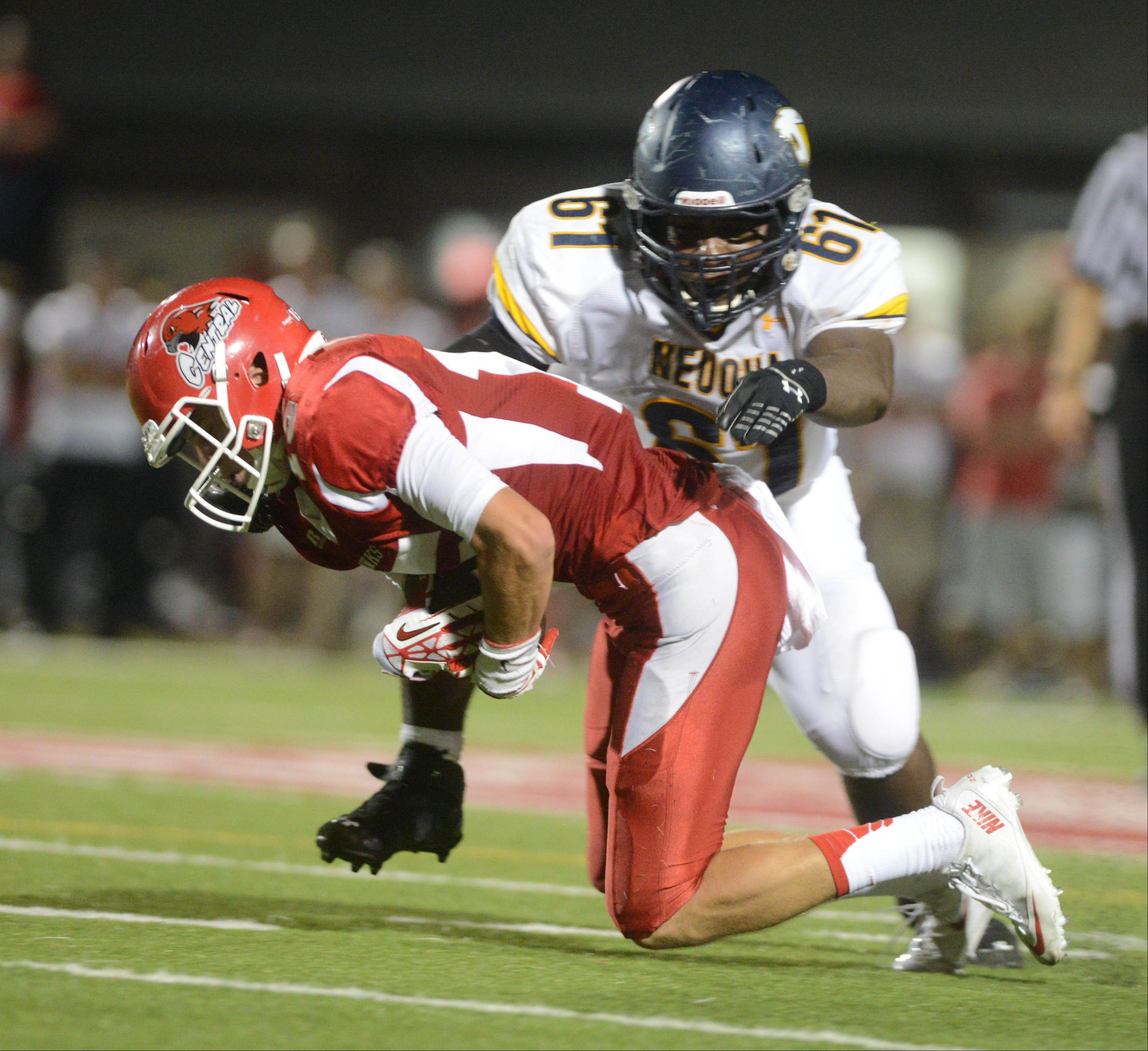 Michael Kolzow of Naperville central,left, is pulled down by Godfrey Collins of Neuqua Valley during game action Friday in Naperville.