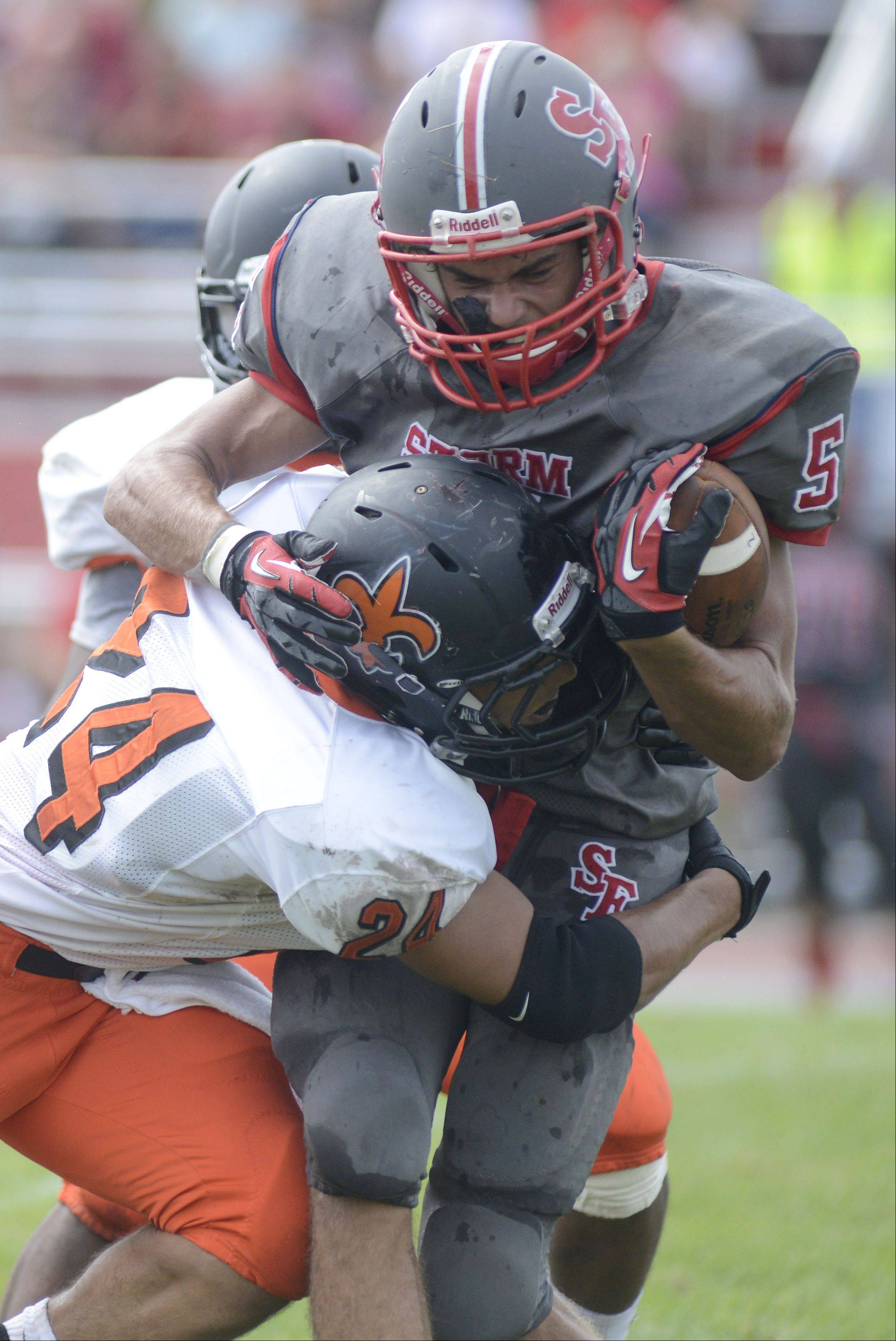South Elgin�s Tyler Christensen is wrapped up by St. Charles East�s Ramon Lopez during Week 1. i