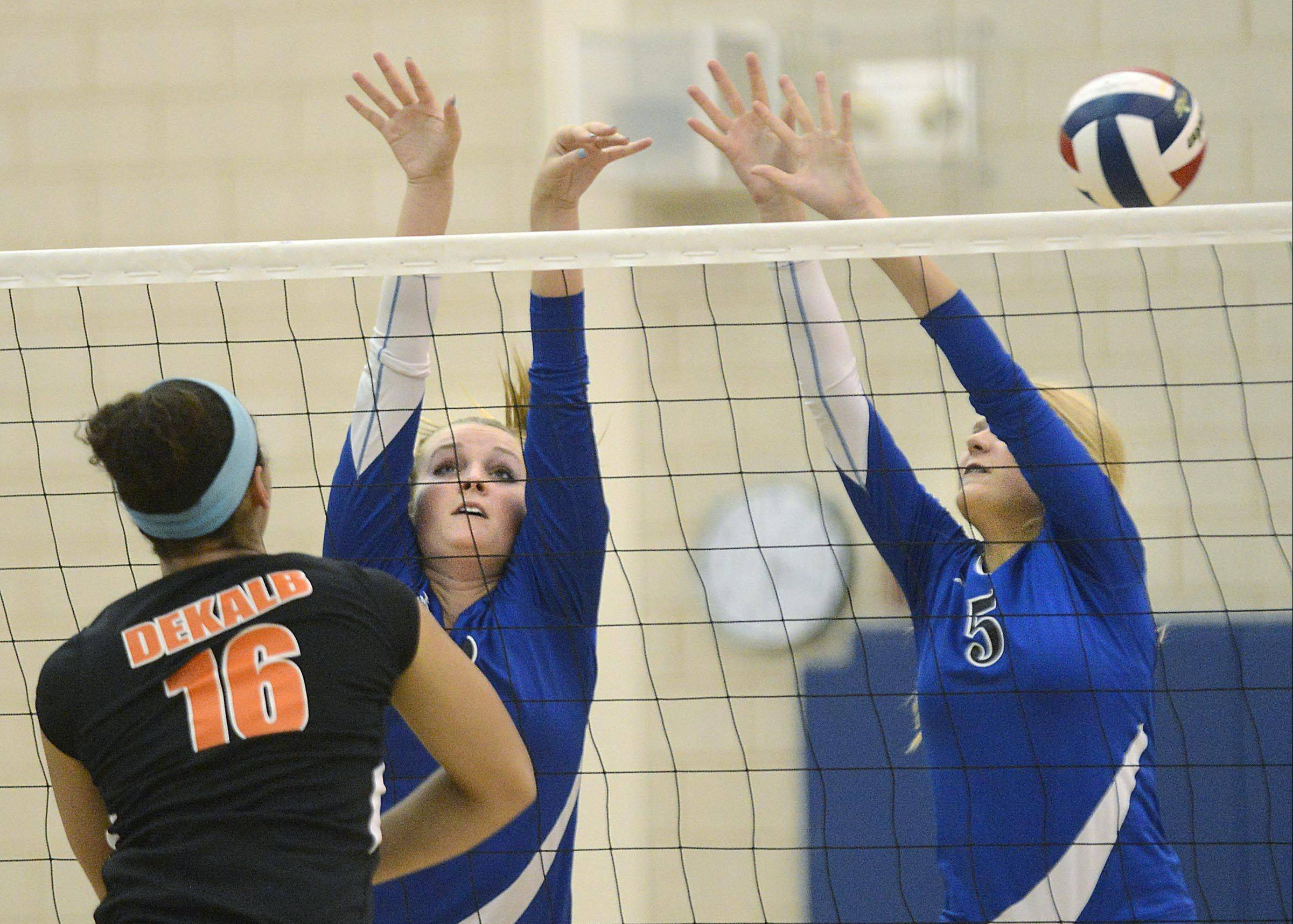 Geneva's Maddie Courter and Kyley Thompson, right, go up for the block against DeKalb's Alexis Hammond Thursday in Geneva.