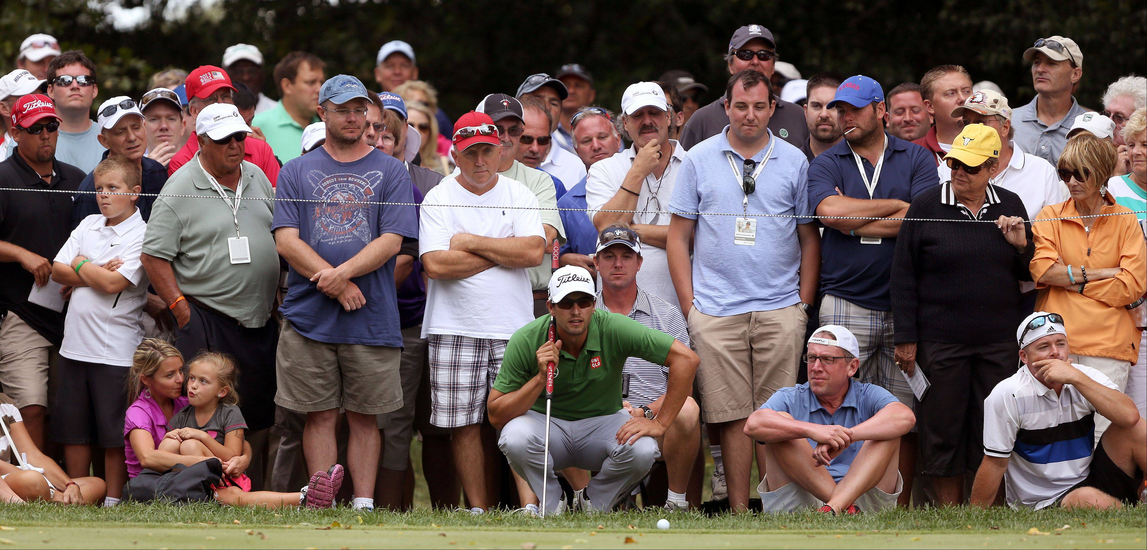 Adam Scott lines up a putt on the 9th hole as the crowd watches during the first-round of the BMW Championship at Conway Farms Golf Club in Lake Forest Thursday.