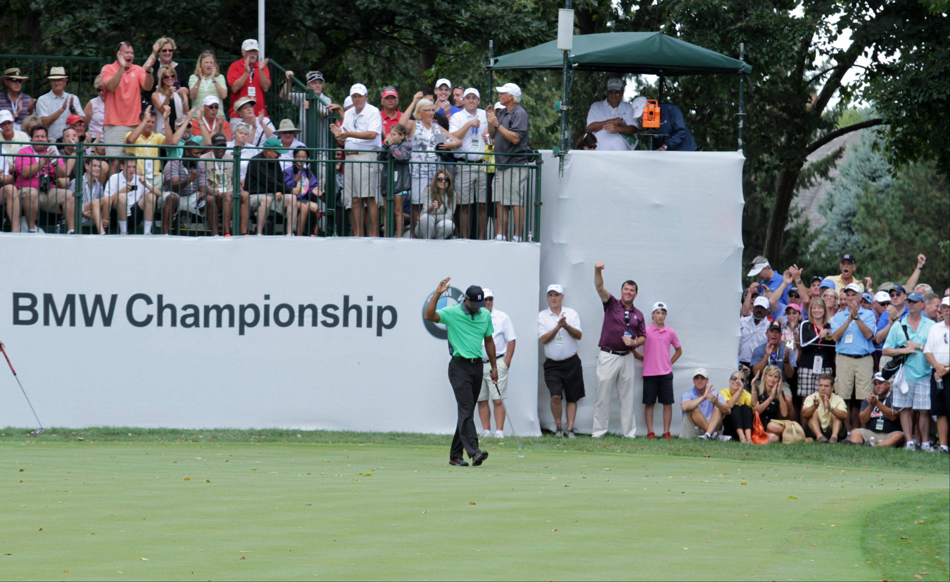 Fans cheer as Tiger Woods sinks a put on the 9th hole.