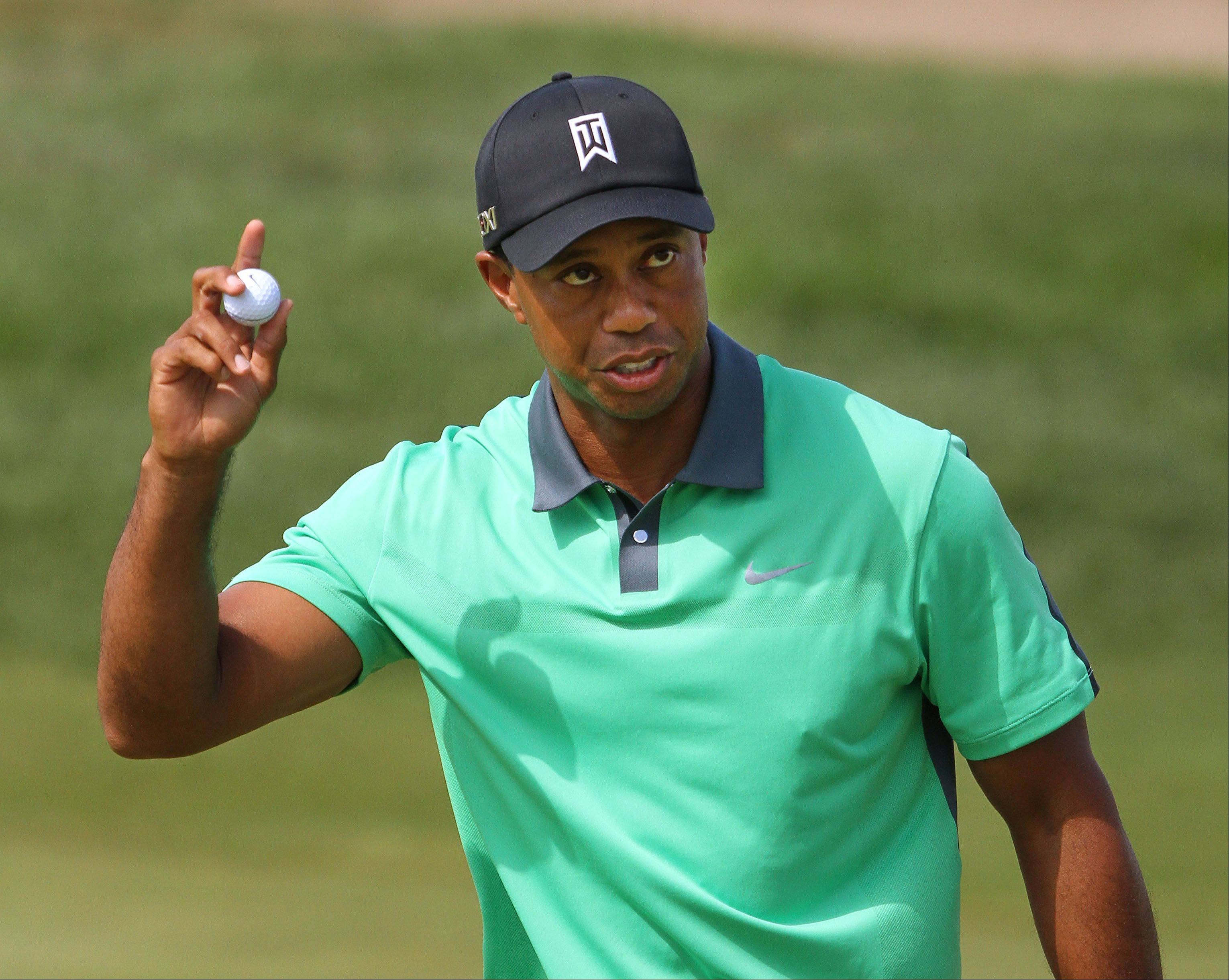 Tiger woods waves to the crowd after making a birdie putt on the 17th hole.