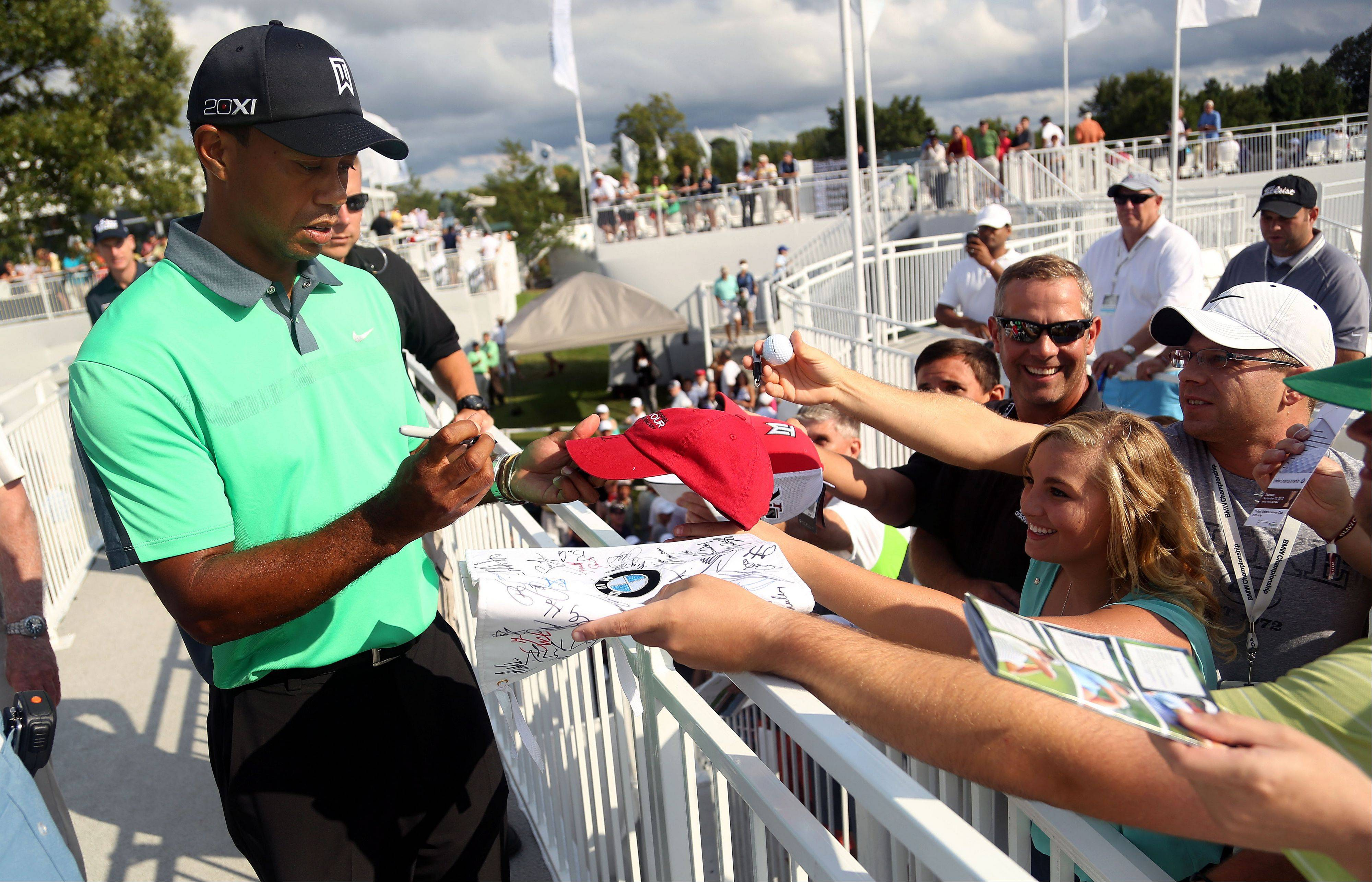 Tiger Woods signs autographs.