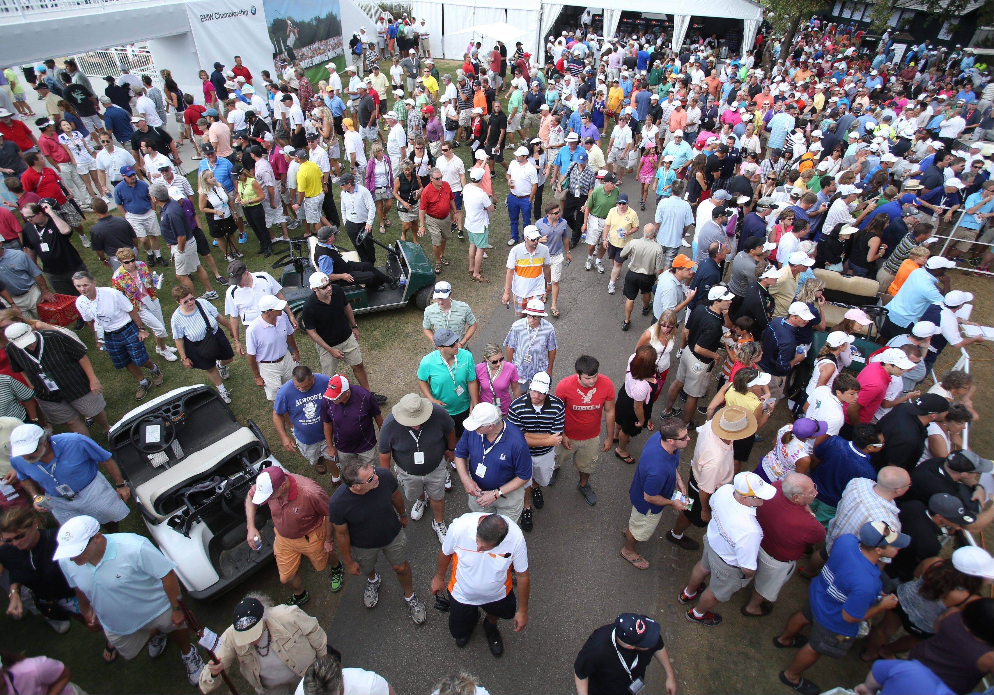 Golf fans walk through a packed walkway.