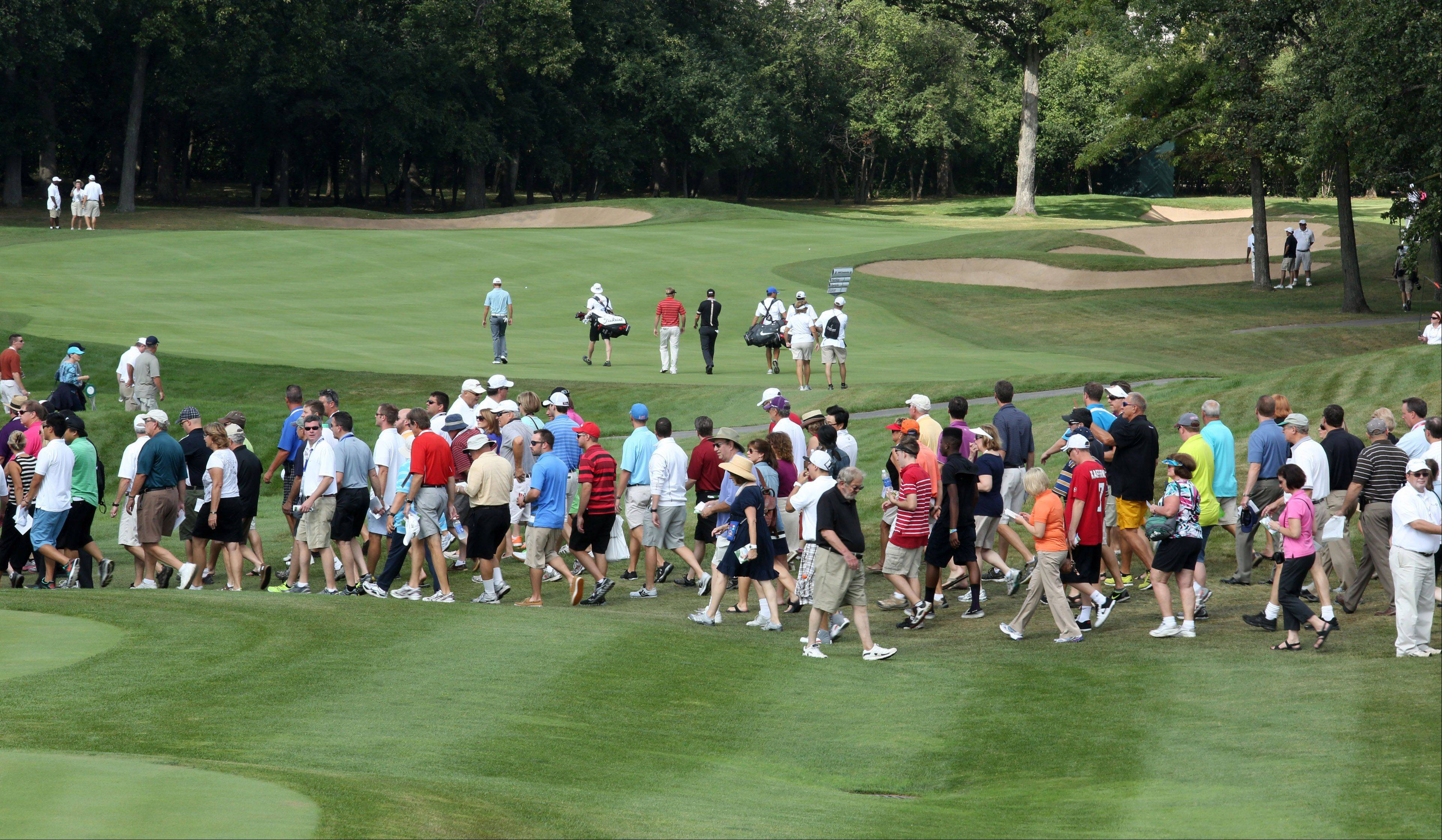 Fans cross the green after golfers in the first group. Russell Henley, John Merrick, and Jimmy Walker teed off on the 1st hole.