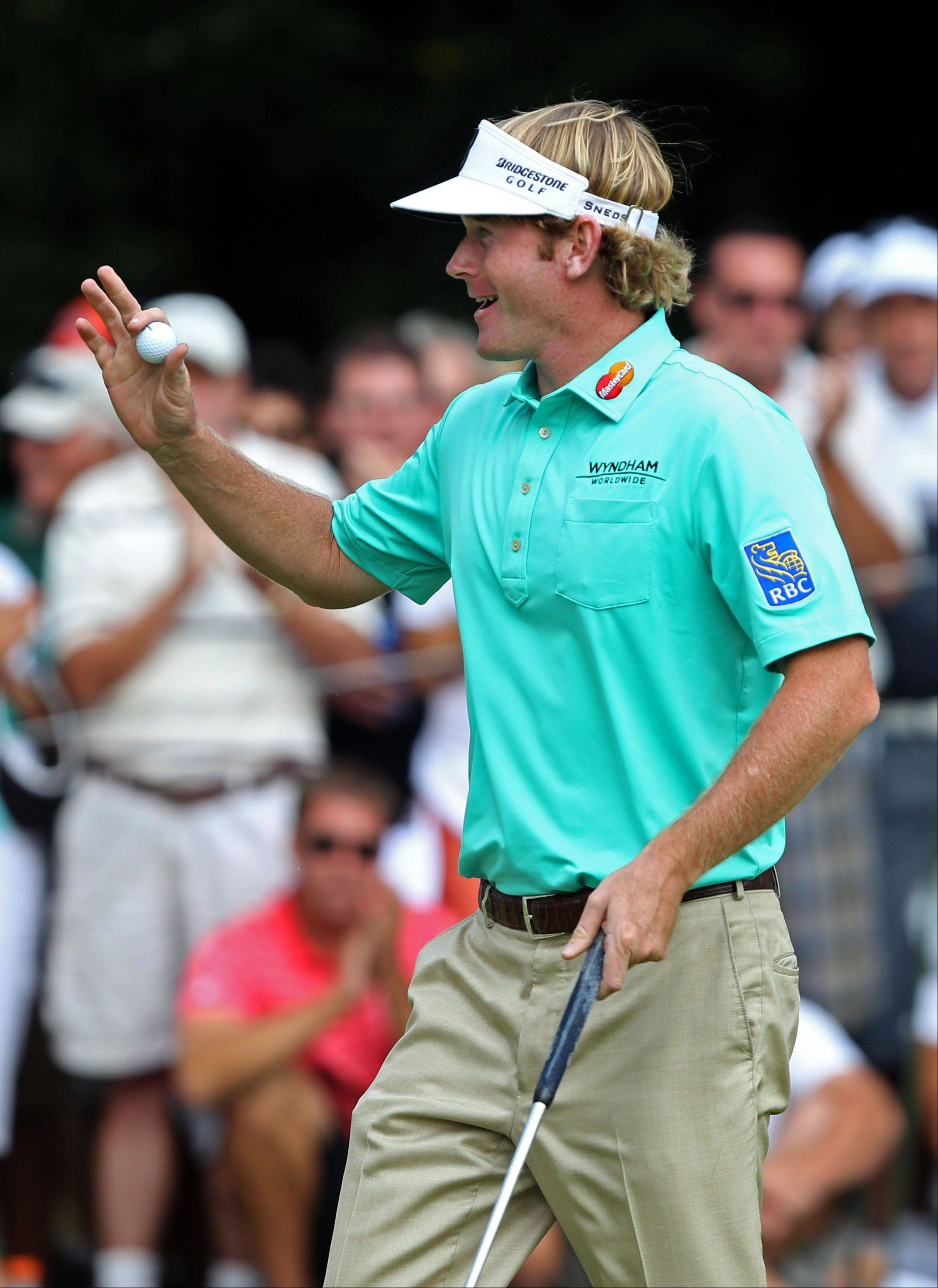 Brandt Snedeker waves after sinking a par putt on the 9th hole.